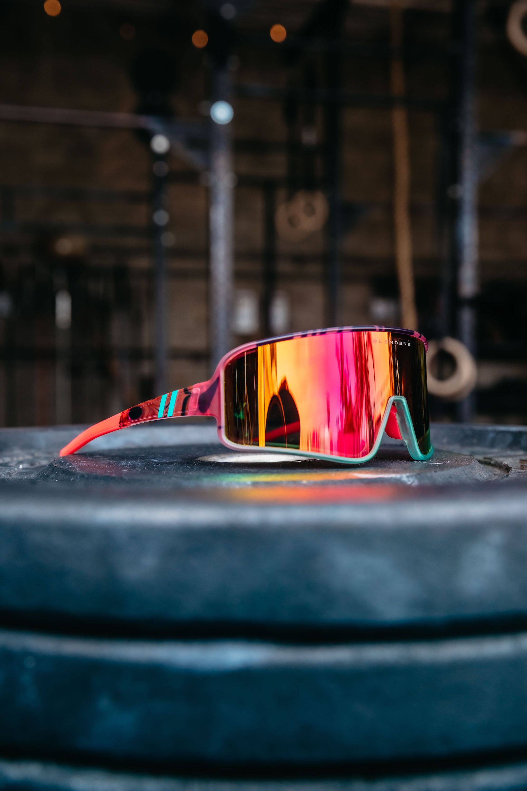 BLENDERS Buttery Bro's signature series sunglasses sitting on weight lifting plates