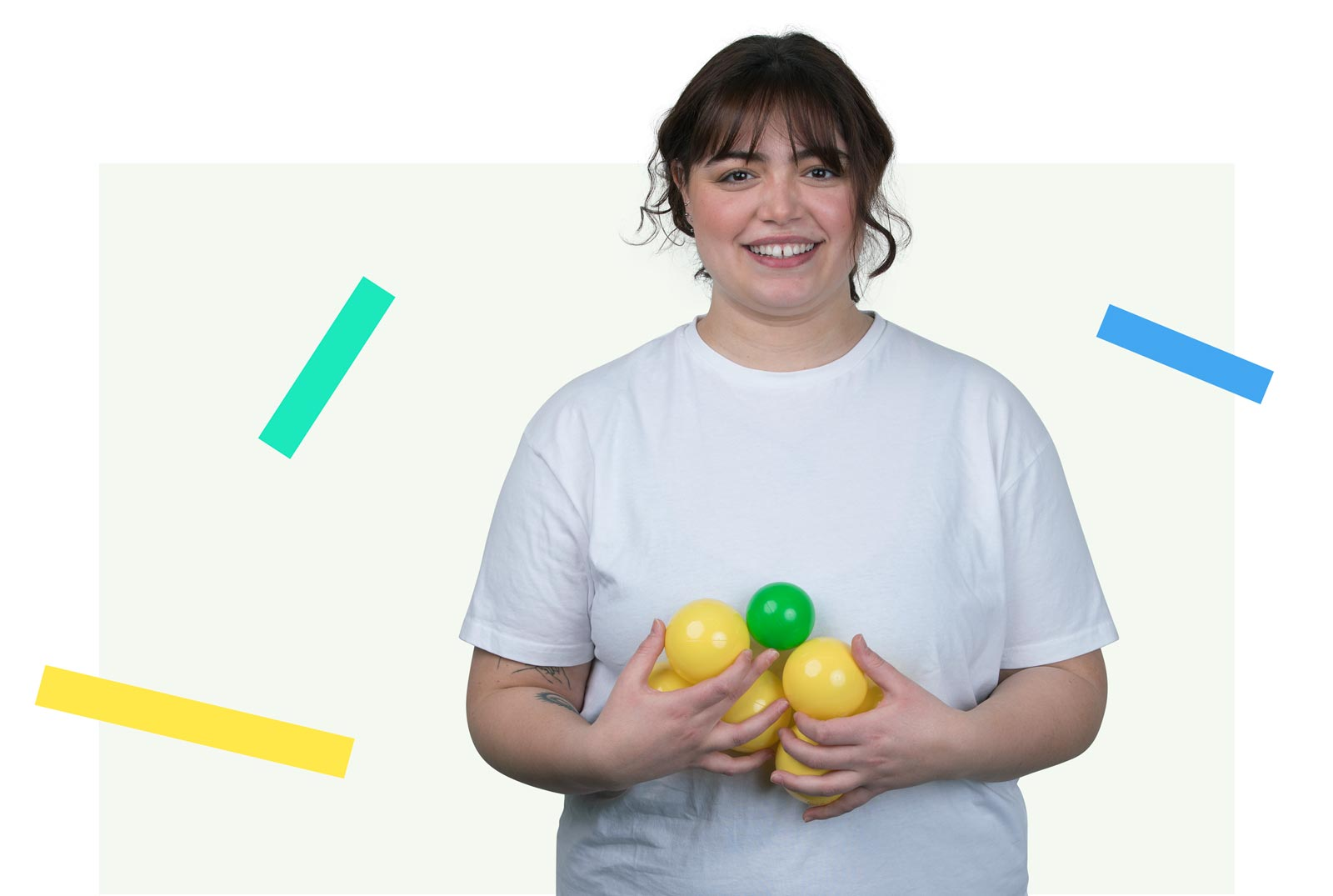An image of a young brunette girl holding yellow and green balls and looking pleased.
