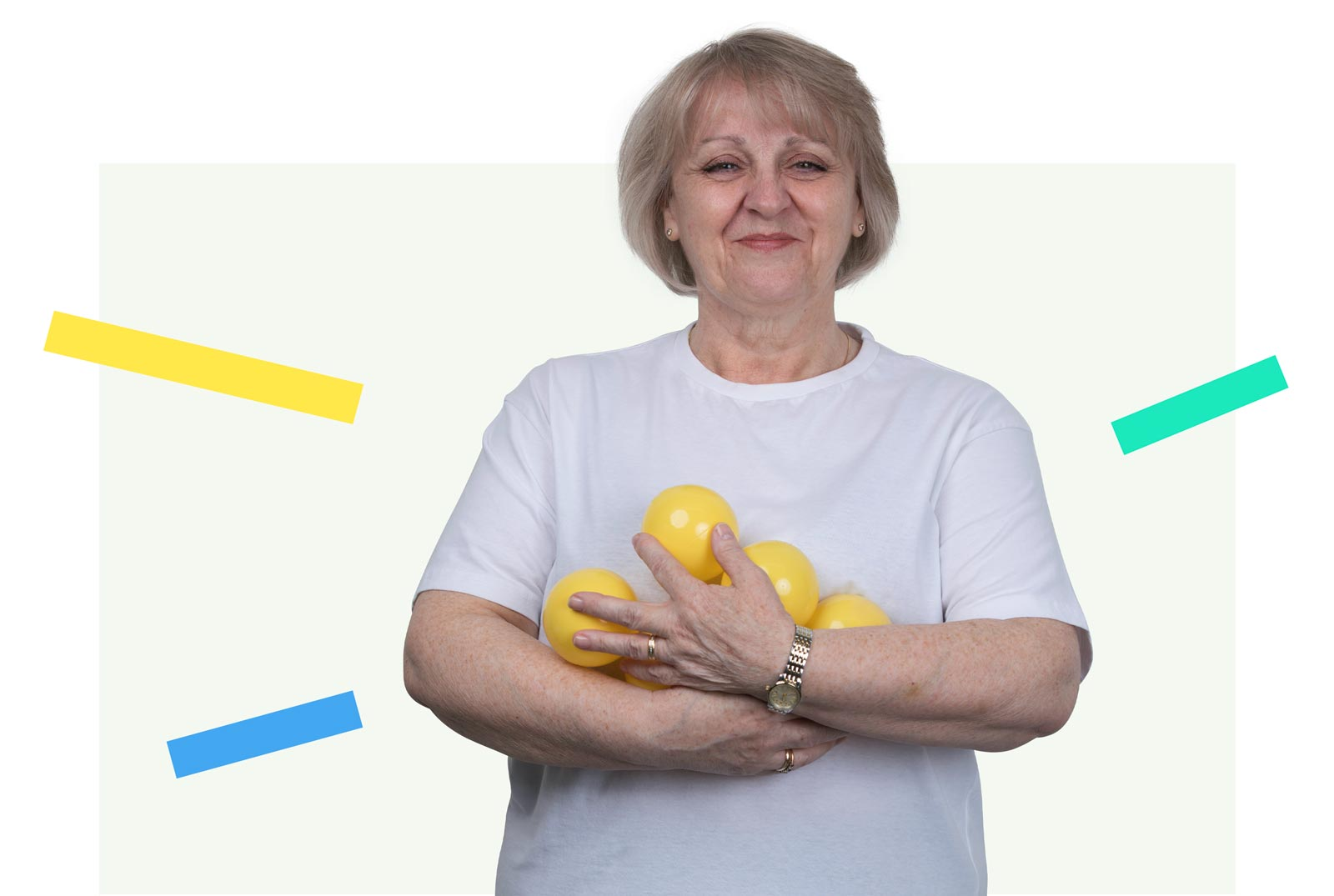 A photo of a blonde woman holding yellow balls and looking pleased.