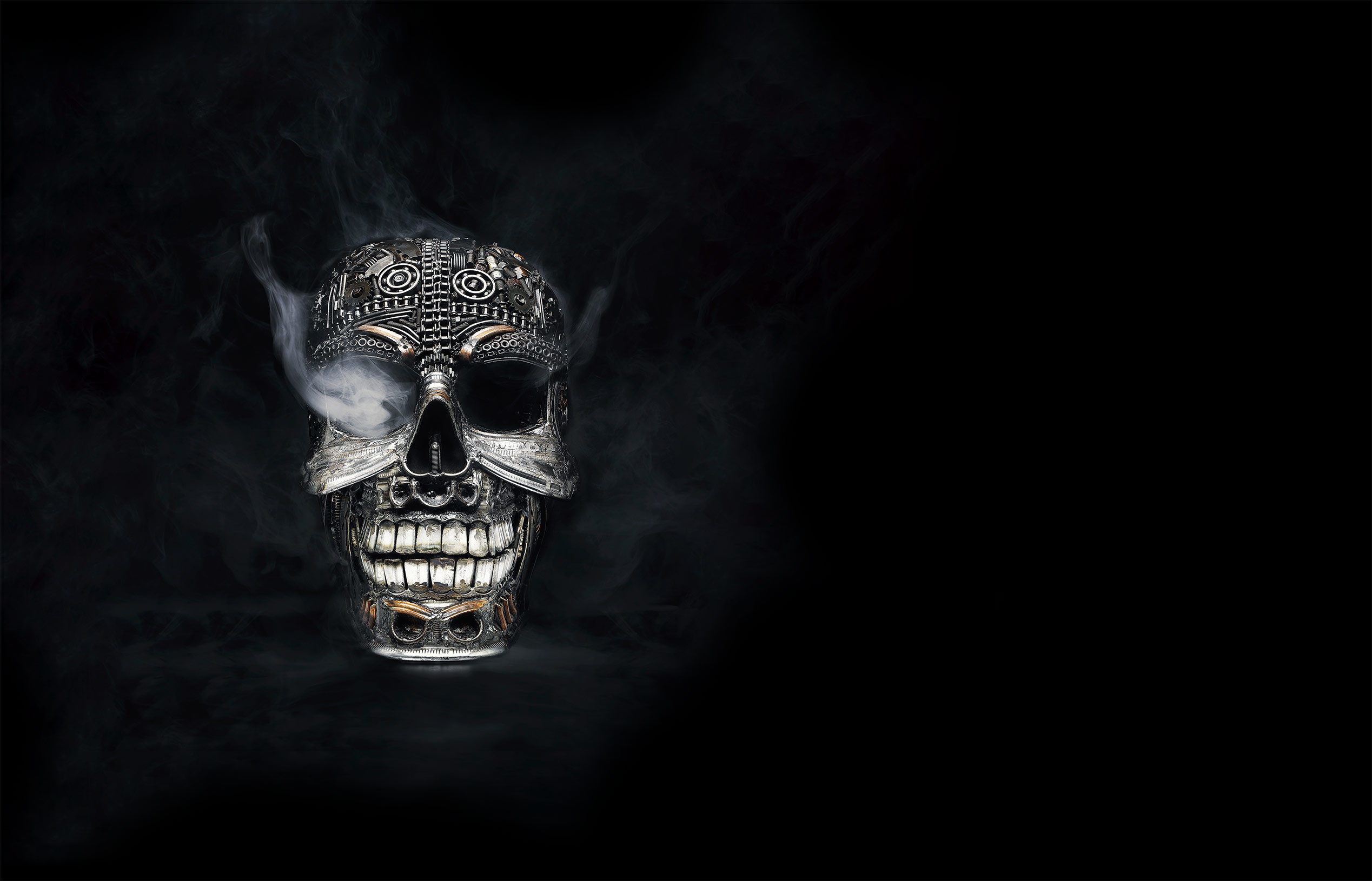 Metal skull before a black background with smoke in one eye product photograph commercial studio artificial light young photographer Philipp Burkart Hamburg