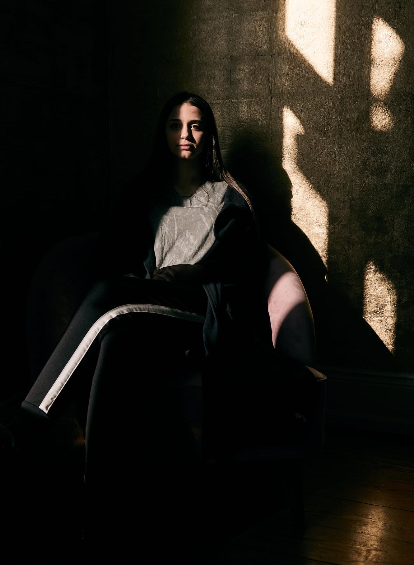 Woman in a jogger pants and hoodie sitting on a chair kissed by the sun sunrays on the wall behind her moody picture, Fashion photography, Philipp Burkart young photographer in Hamburg