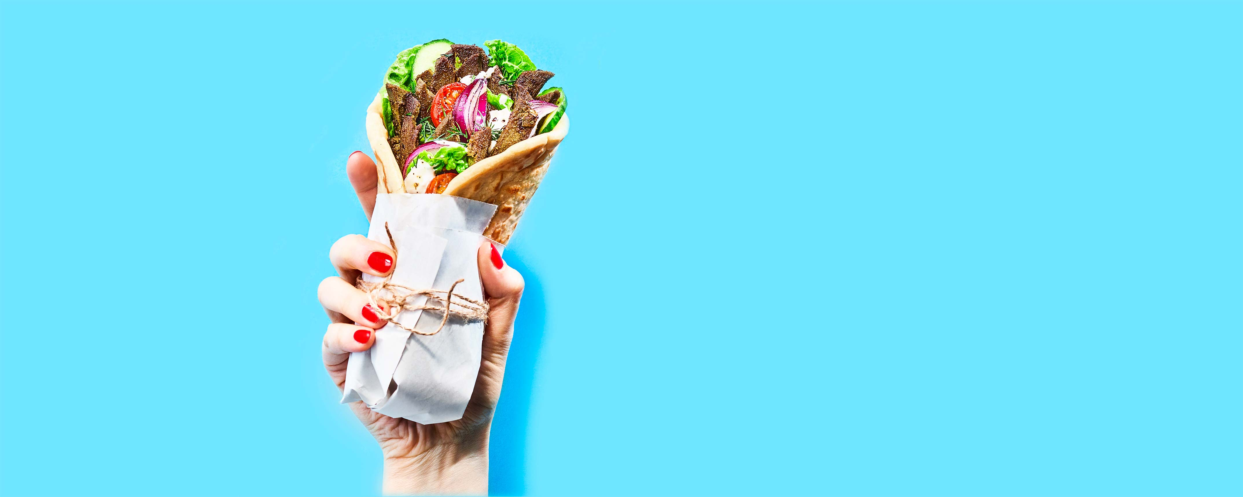 Woman's hand holding a vegeterian wrap food revolution blue Food commercial photography artificial light Philipp Burkart photographer in Hamburg