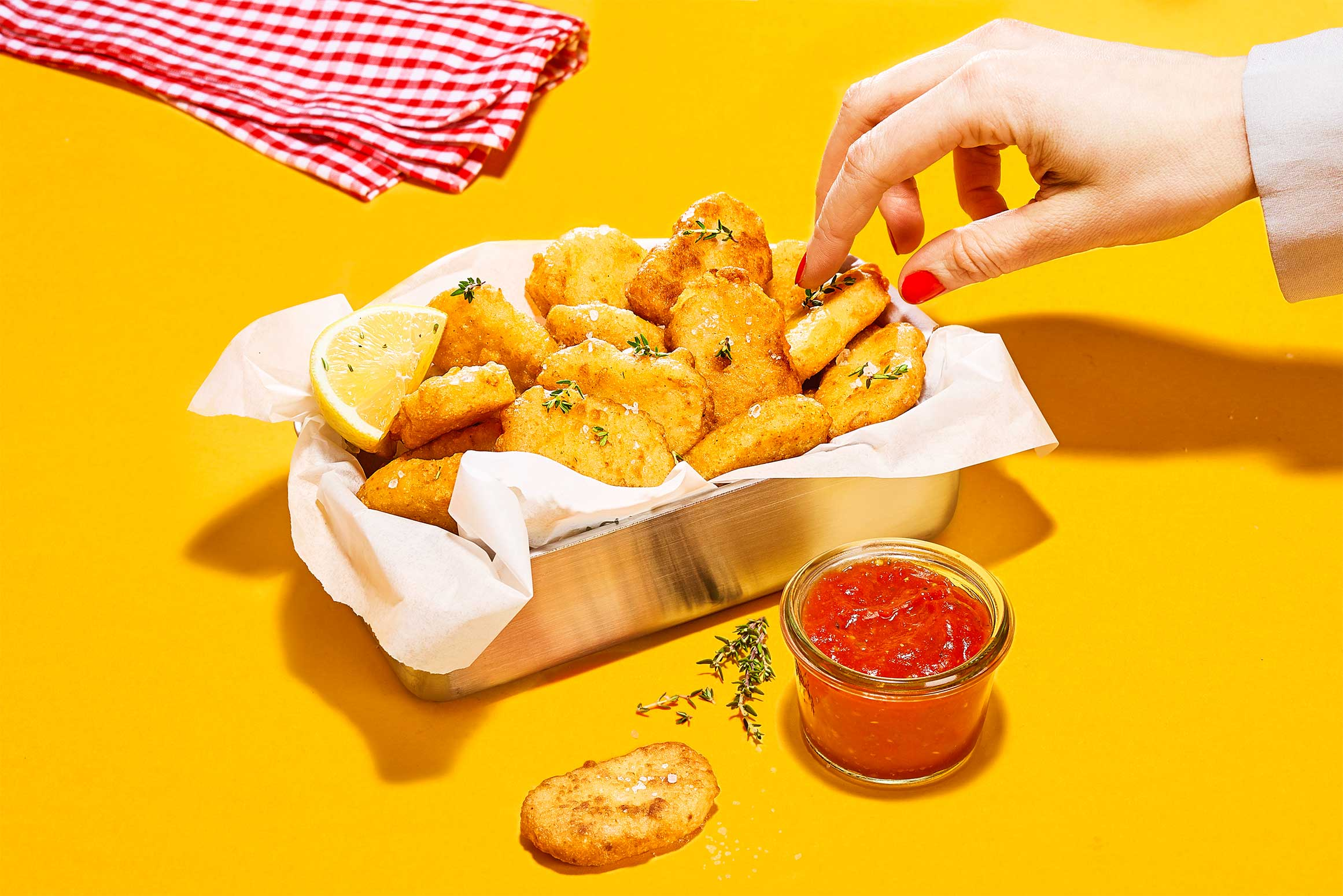 Woman's hand taking a vegeterian nugget made of beans out of a box to dip it in tomate sauce red blanket in the background yellow Food commercial photography artificial light Philipp Burkart photographer in Hamburg