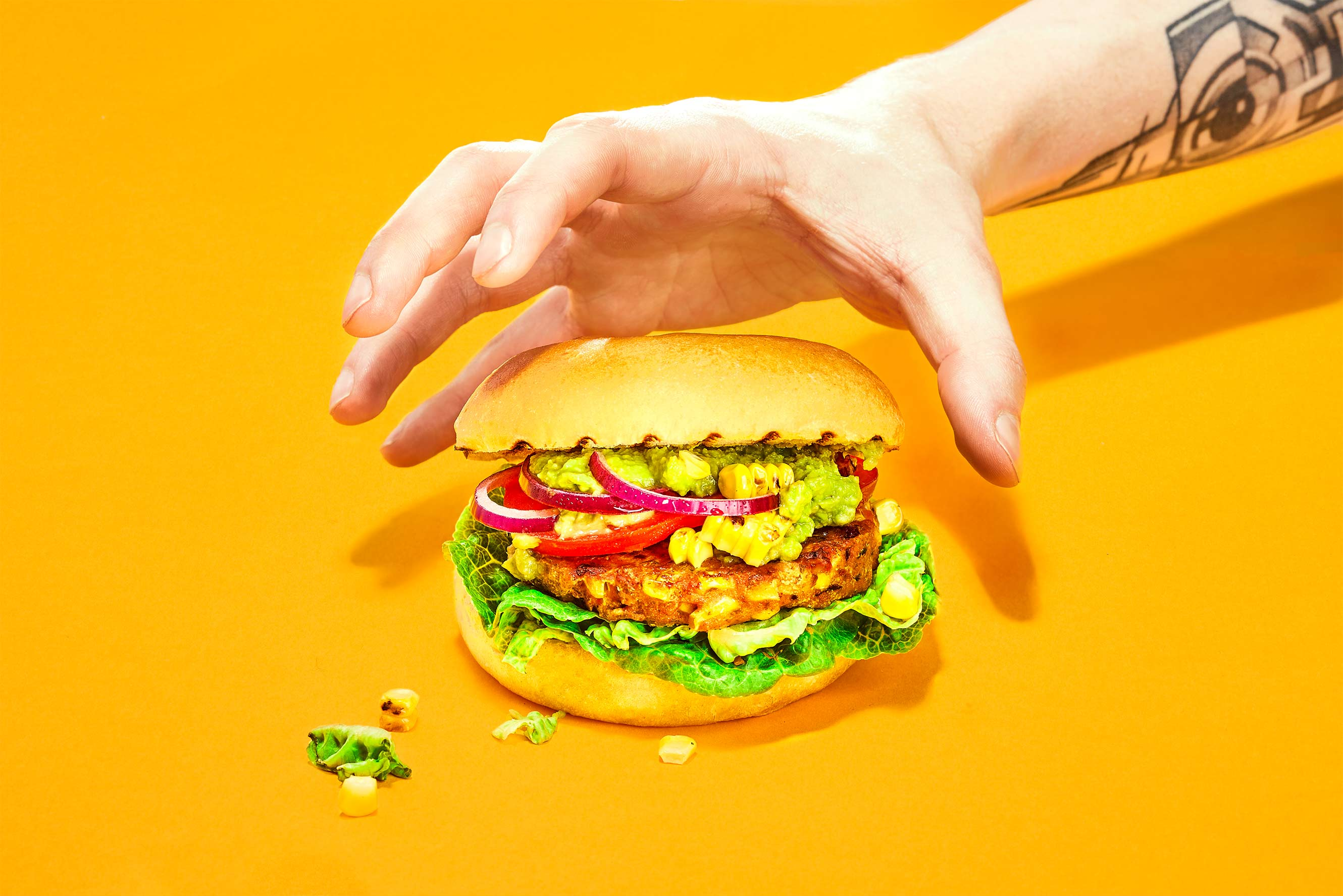 Tattooed man's arm grabbing a tex mex burger with a patty made of buffalo worms Food commercial photography artificial light Philipp Burkart photographer in Hamburg Chewow
