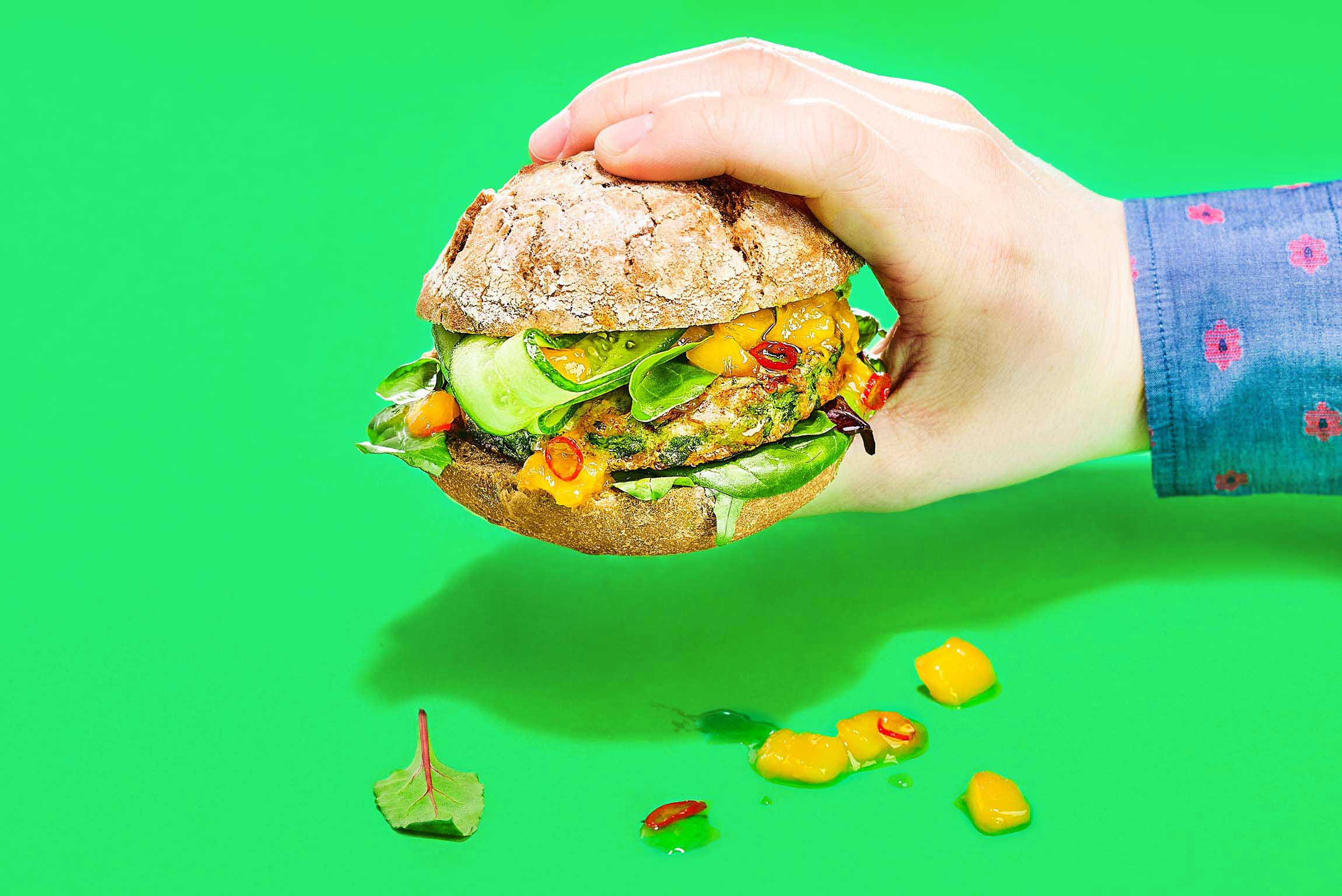 Man's hand holding a spinache burger with a buffalo worms patty Food commercial photography artificial light Philipp Burkart photographer in Hamburg