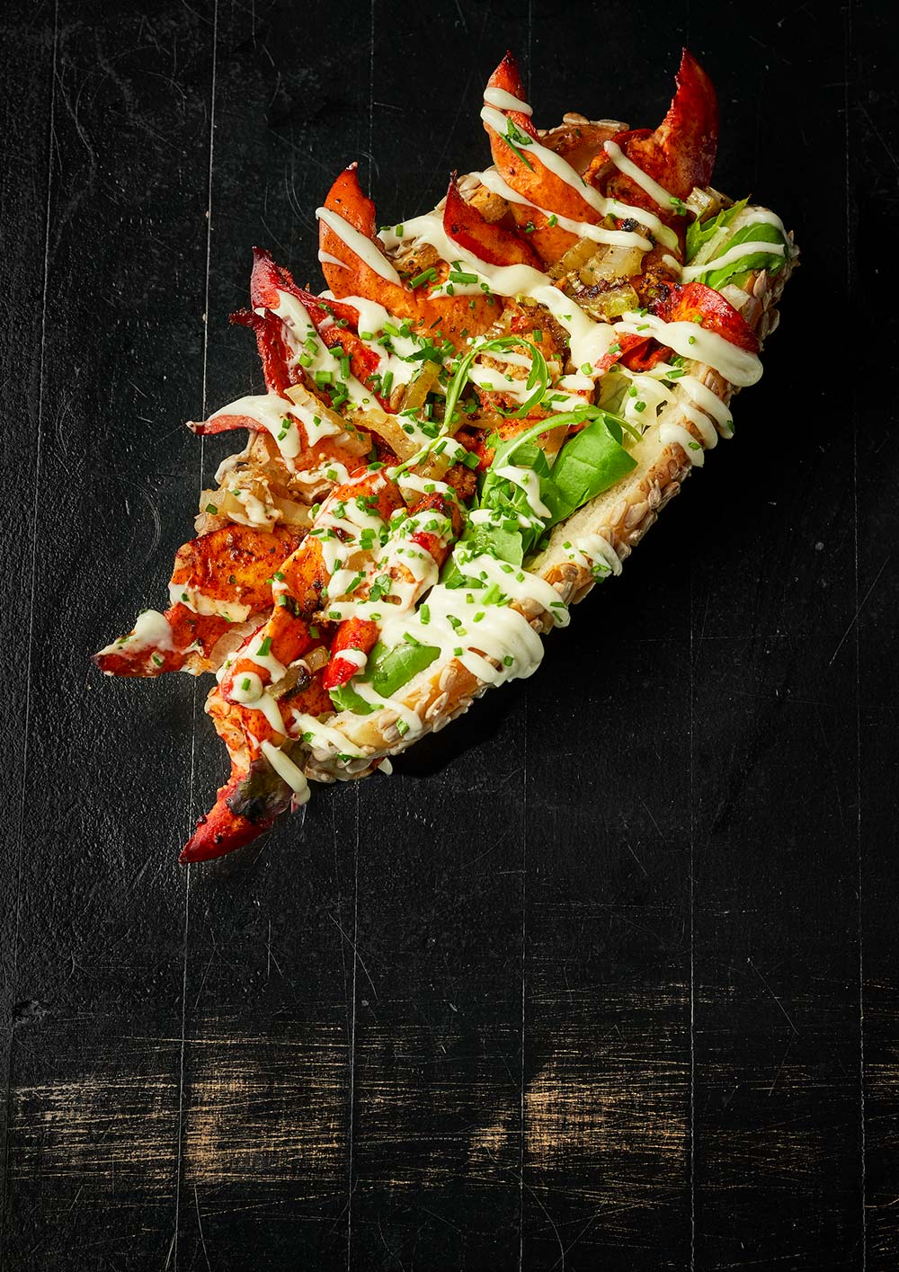 Food lobster roll on a black table with yellow scratches food commercial photography Philipp Burkart young photographer in Hamburg