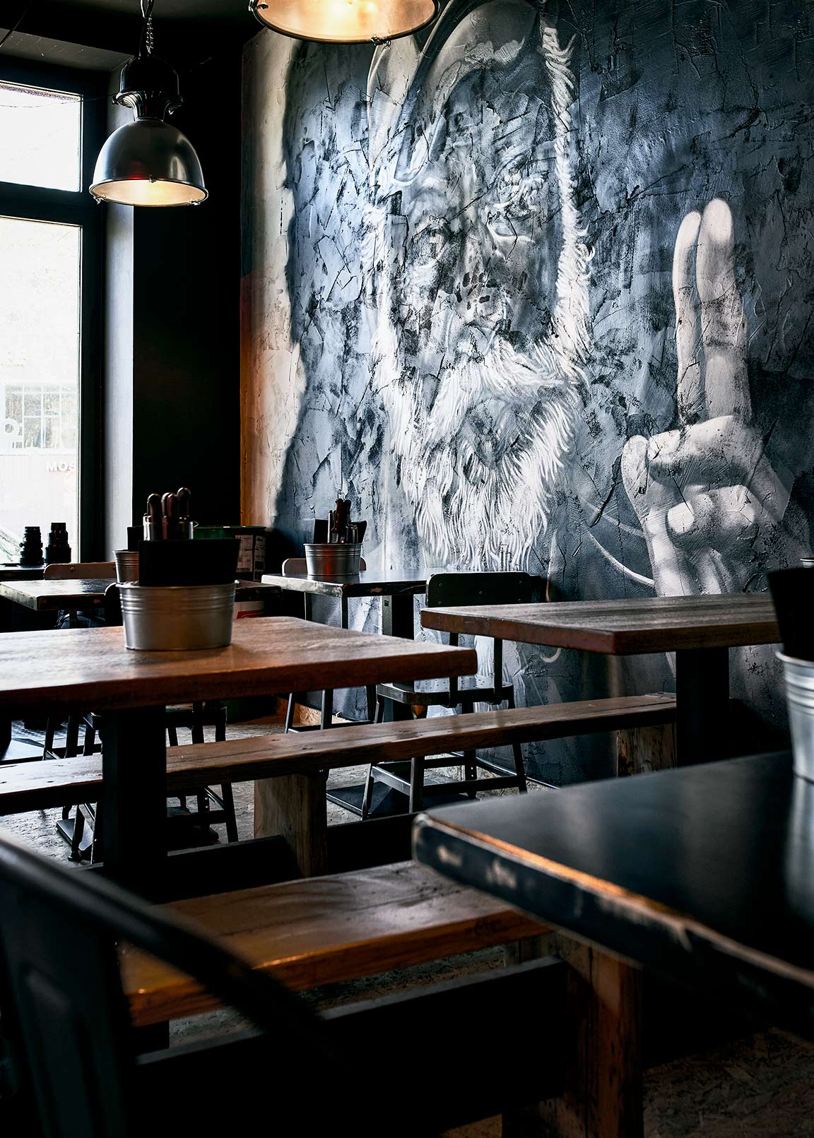 Chairs and tables in a restaurant with a painting of a captain showing the victory symbol with his fingers food commercial photography Philipp Burkart young photographer in Hamburg