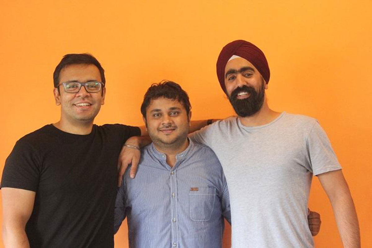 Akshay, CEO, Maddy, CTO and Jaideep, CMOO against an orange backdrop