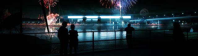 Dramatic night project visualisation: blue light coming from a museum building reflected in water, fireworks, dark silhouettes
