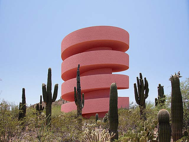 Photomontage: various cacti surounding a pink building in the desert
