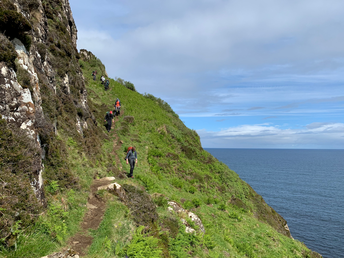 people hike the Skye Trail near the sea