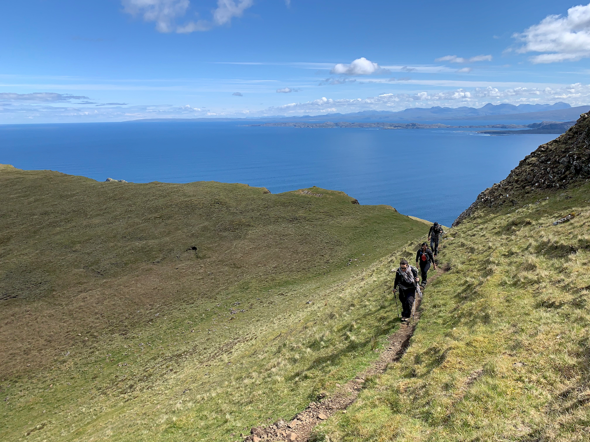 Hikers walk along the cliffside of Skye