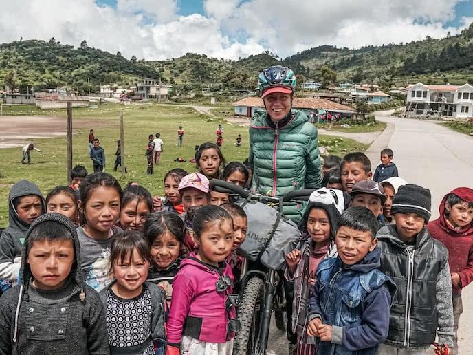 Bikepacker on mountain bike with school children