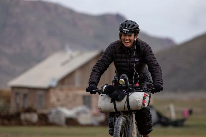 lael wilcox biking on her mountain bike with bikepacking bags