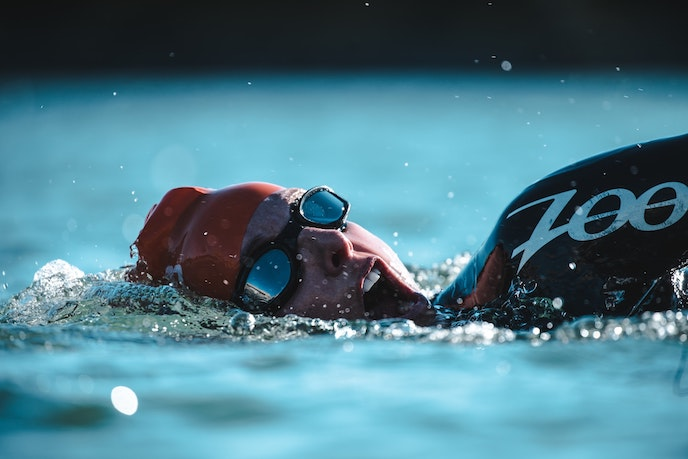 triathlete swil swimming with wetsuit cap and goggles