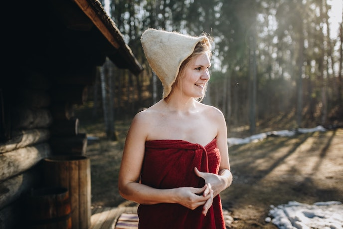 woman with towel and hat outside finnish sauna