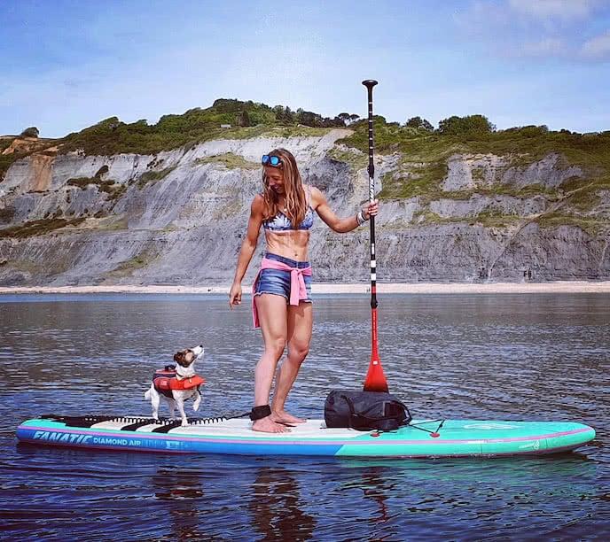 Paddleboarder sup paddling with dog
