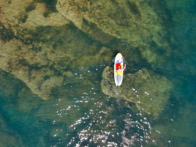 SUP paddle boarding in sea overhead