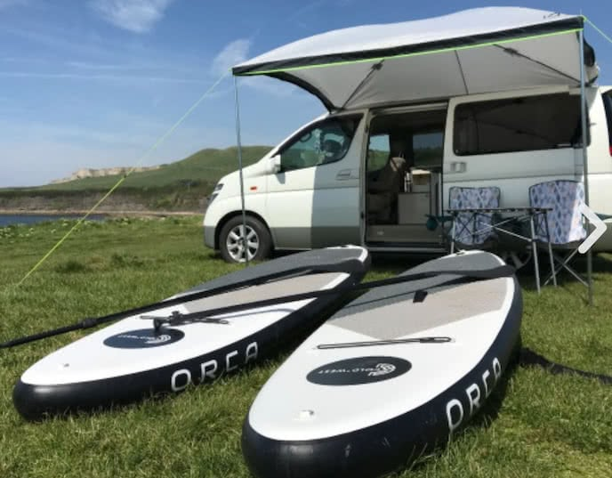 Campervan with paddleboards and camping chairs Bournemouth UK