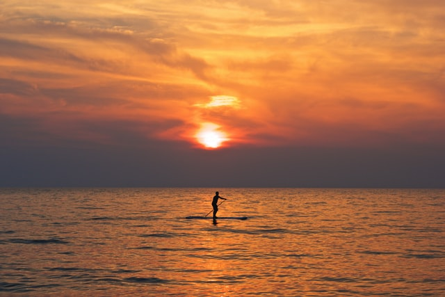 man paddleboarding sup at sunset