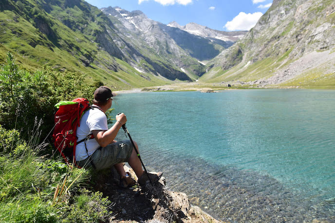 hikers on walking holiday france by mountain lake pyrenees