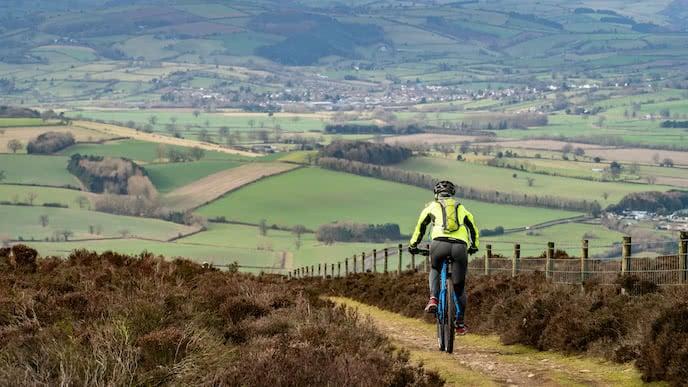 female mountain biker bikes countryside trail
