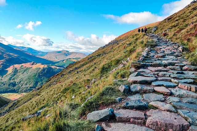 gray rocky pathway on green grass field near mountains under blue sky during daytime