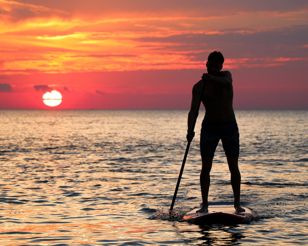 Forward stroke paddling into the sunset on flat water