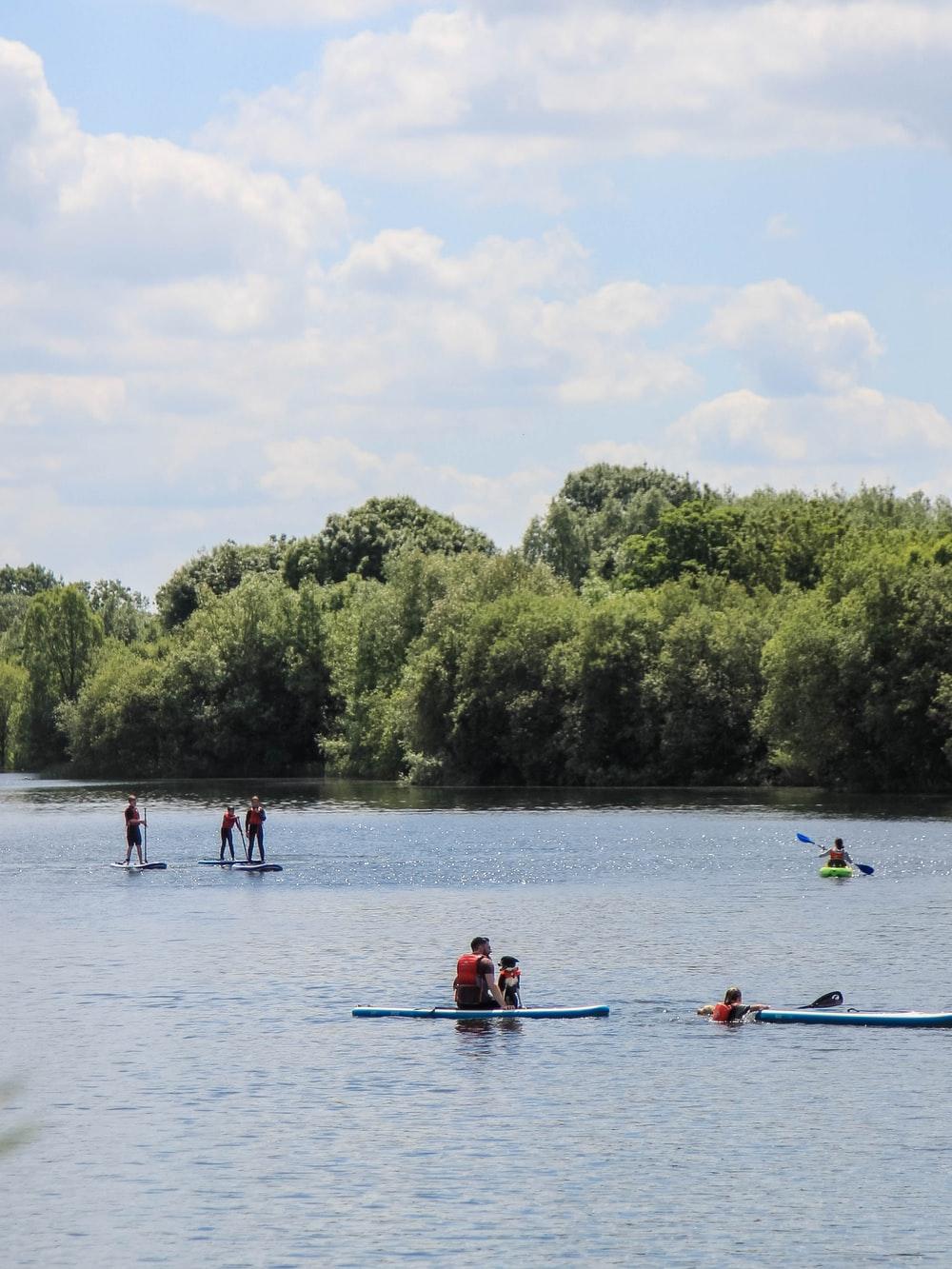 people riding on kayak near trees during daytime