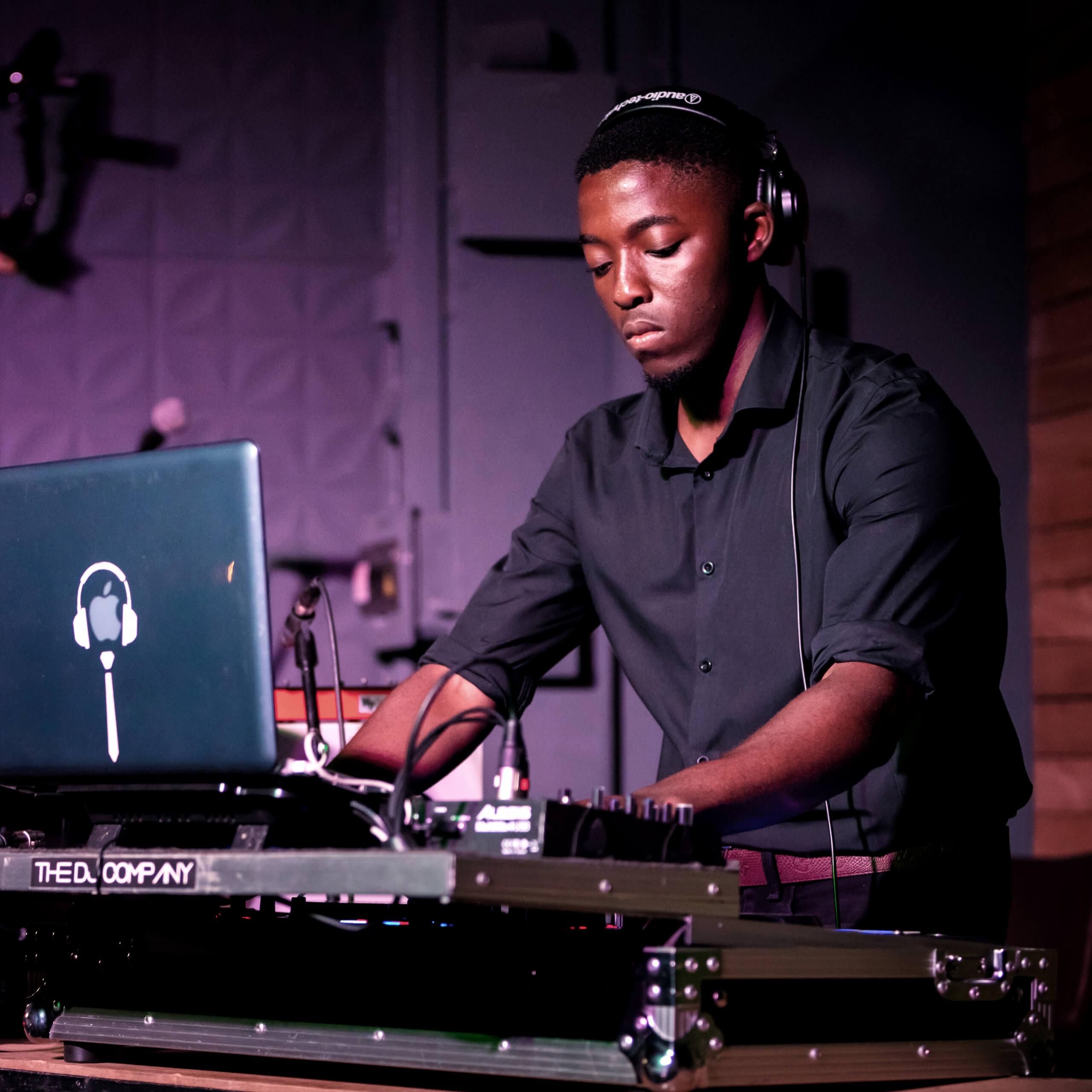 Cape Town Wedding DJ Jacky Masutha holding his headphones while DJing.