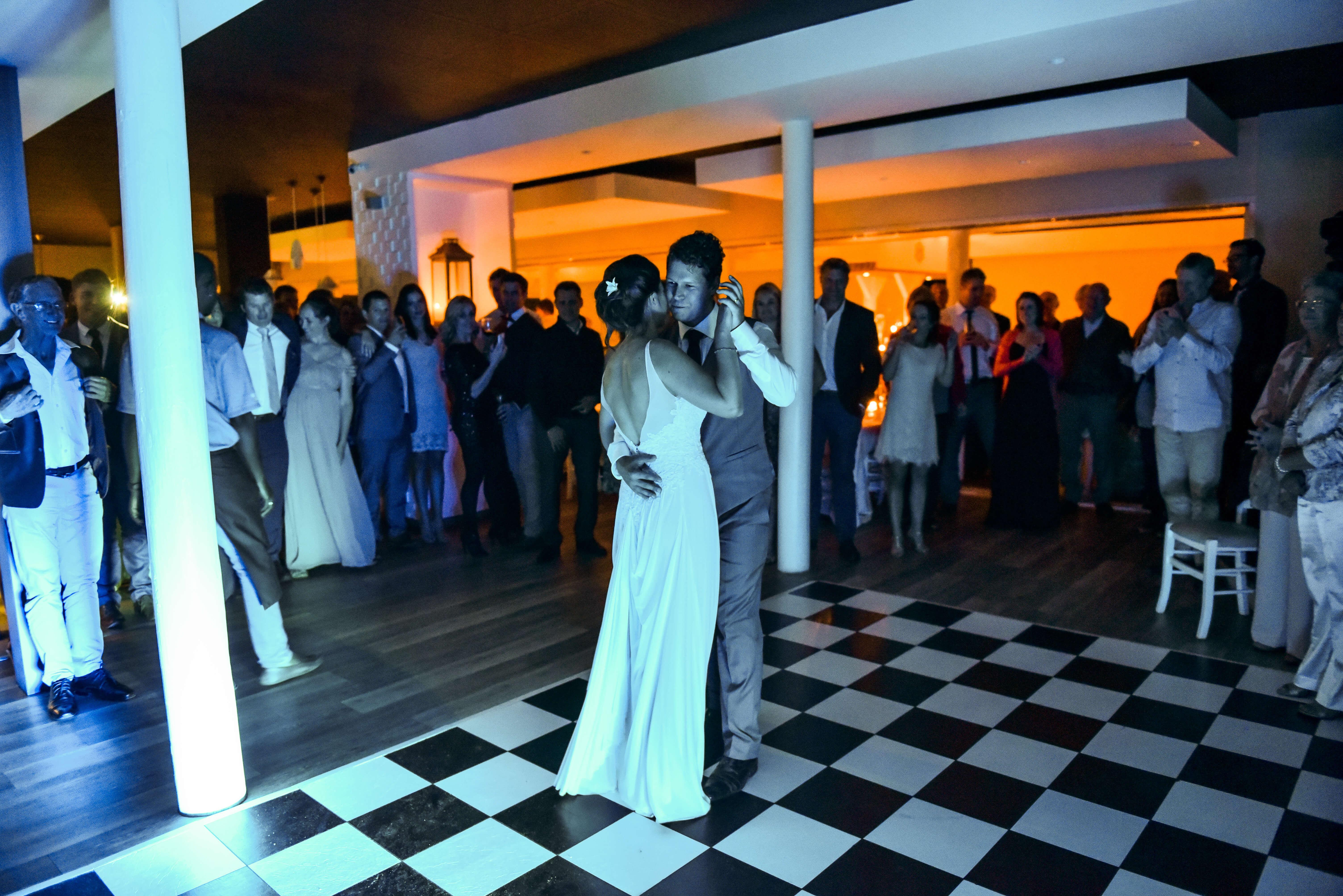 A bride and groom dancing at their Plett wedding on a blue lit dance floor.