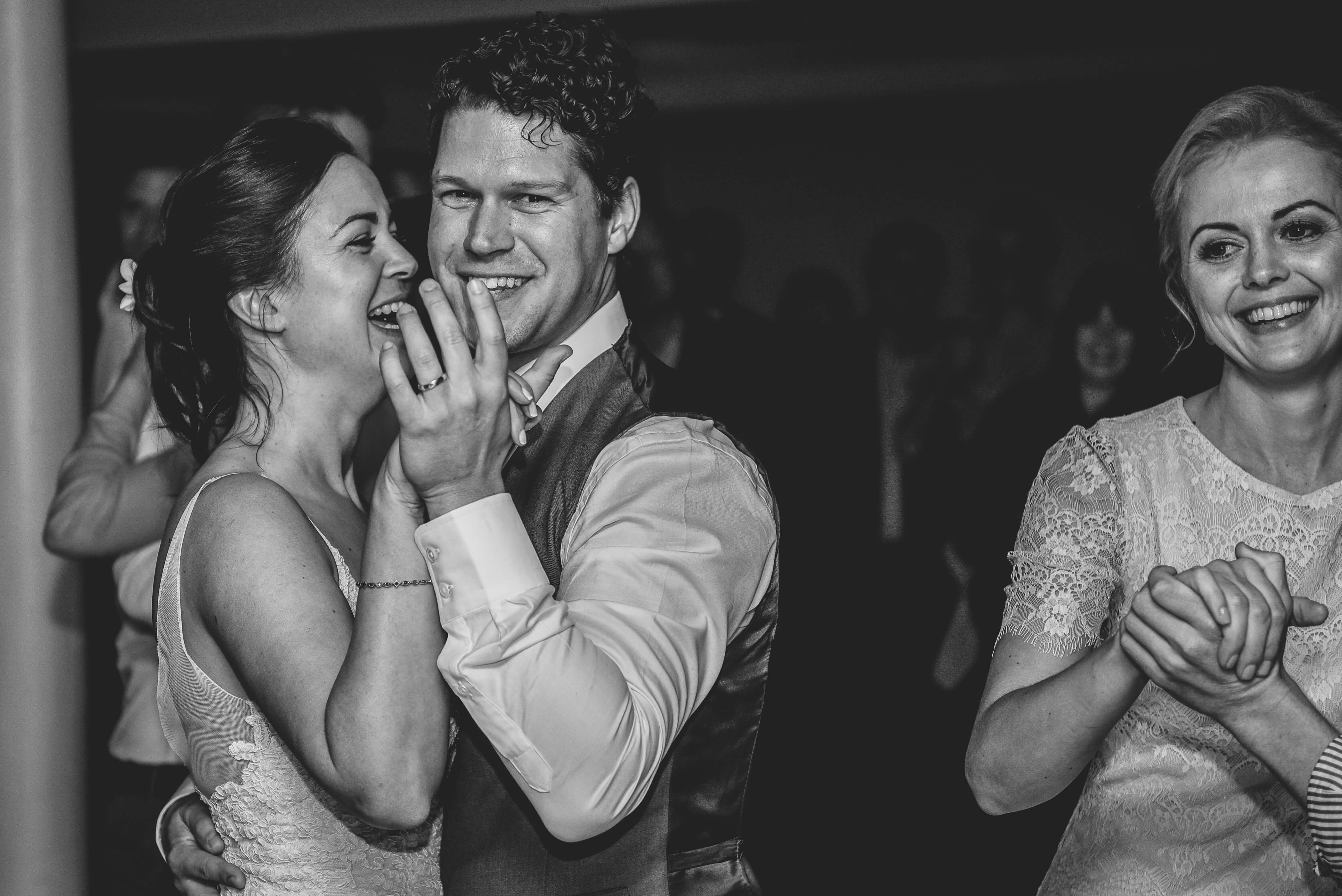 A bride and groom holding hands, smiling and laughing on their wedding night.