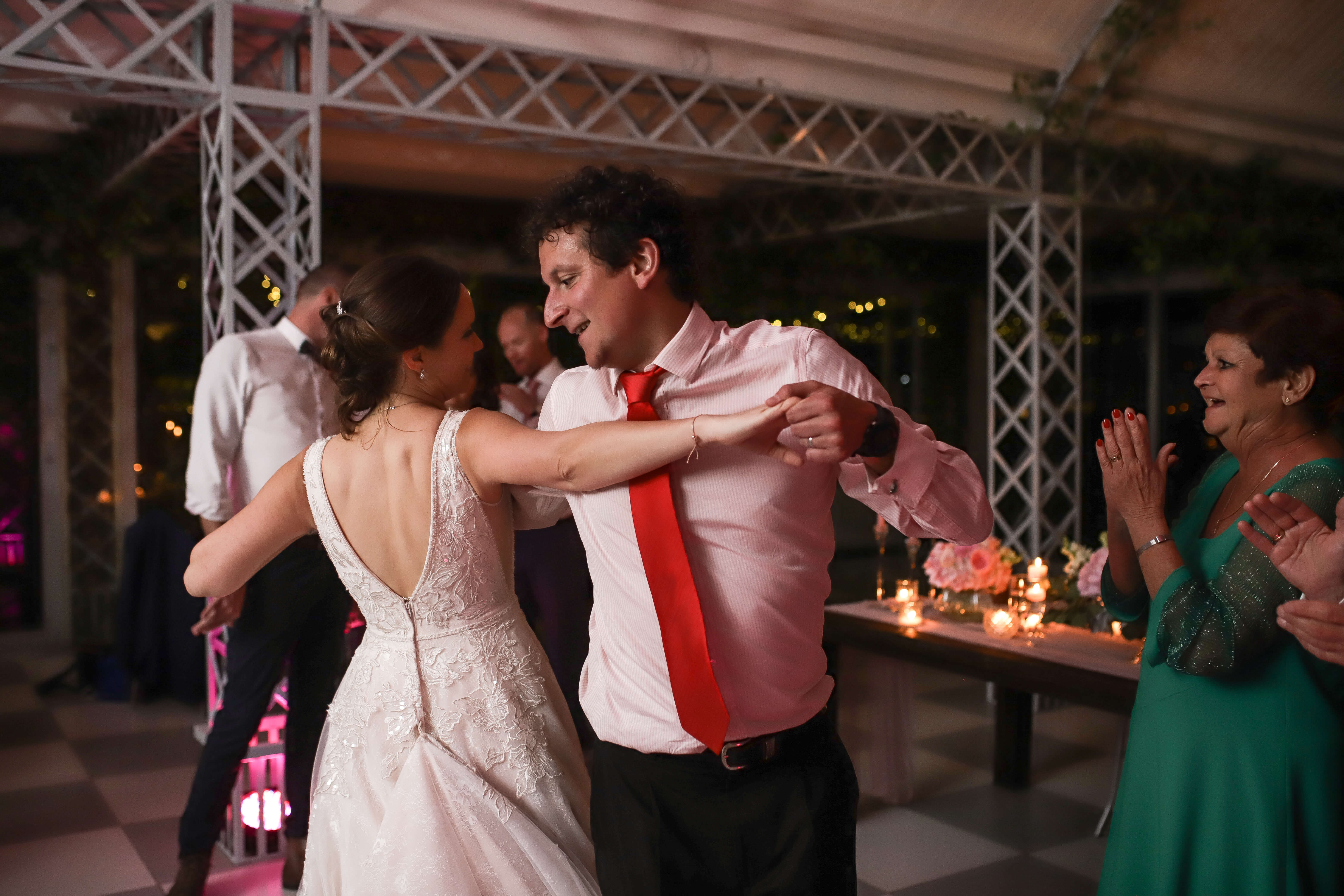 A bride and her friend dancing and swaying on her wedding night.
