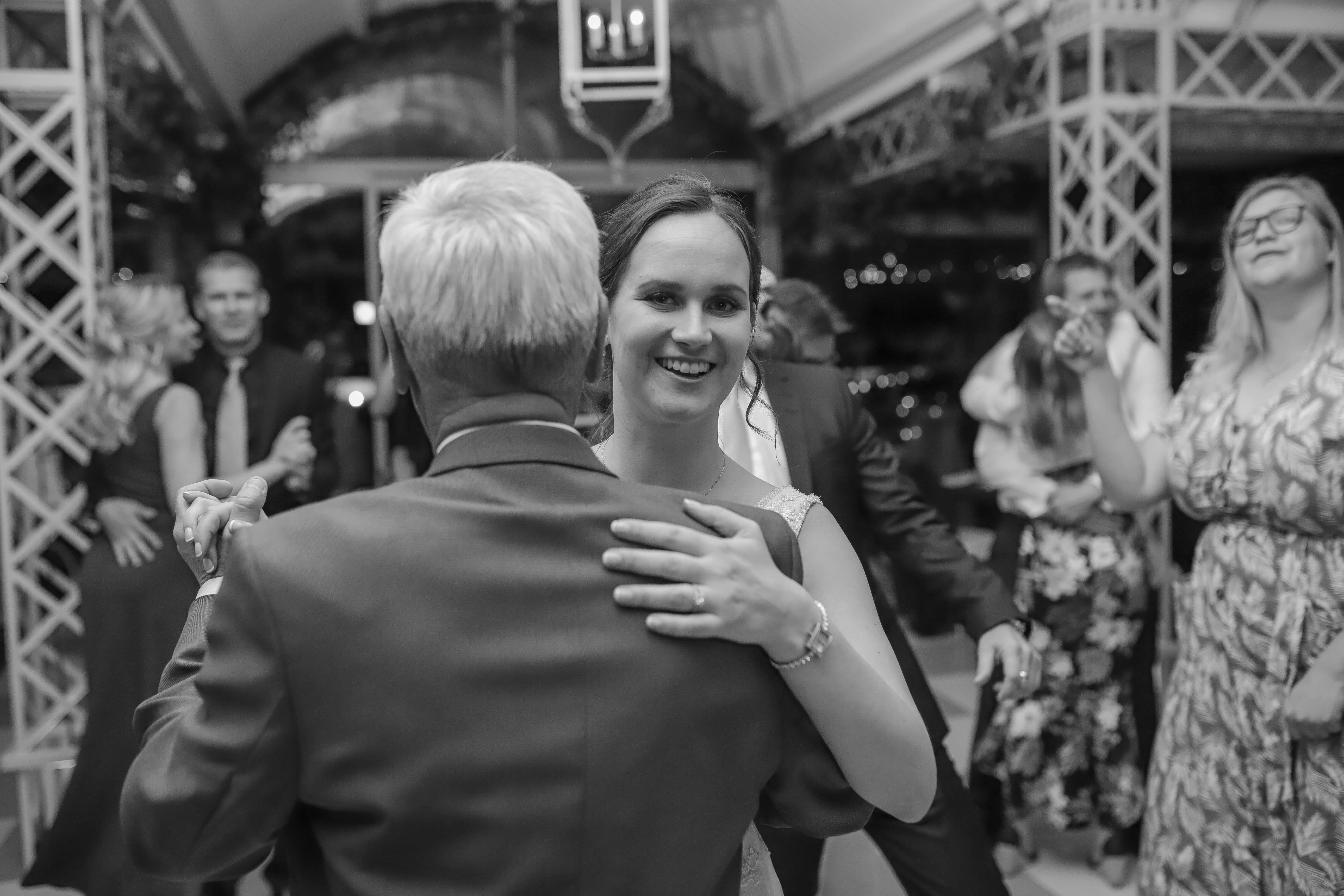 A bride smiling looking at the camera, while holding her father who is facing away.