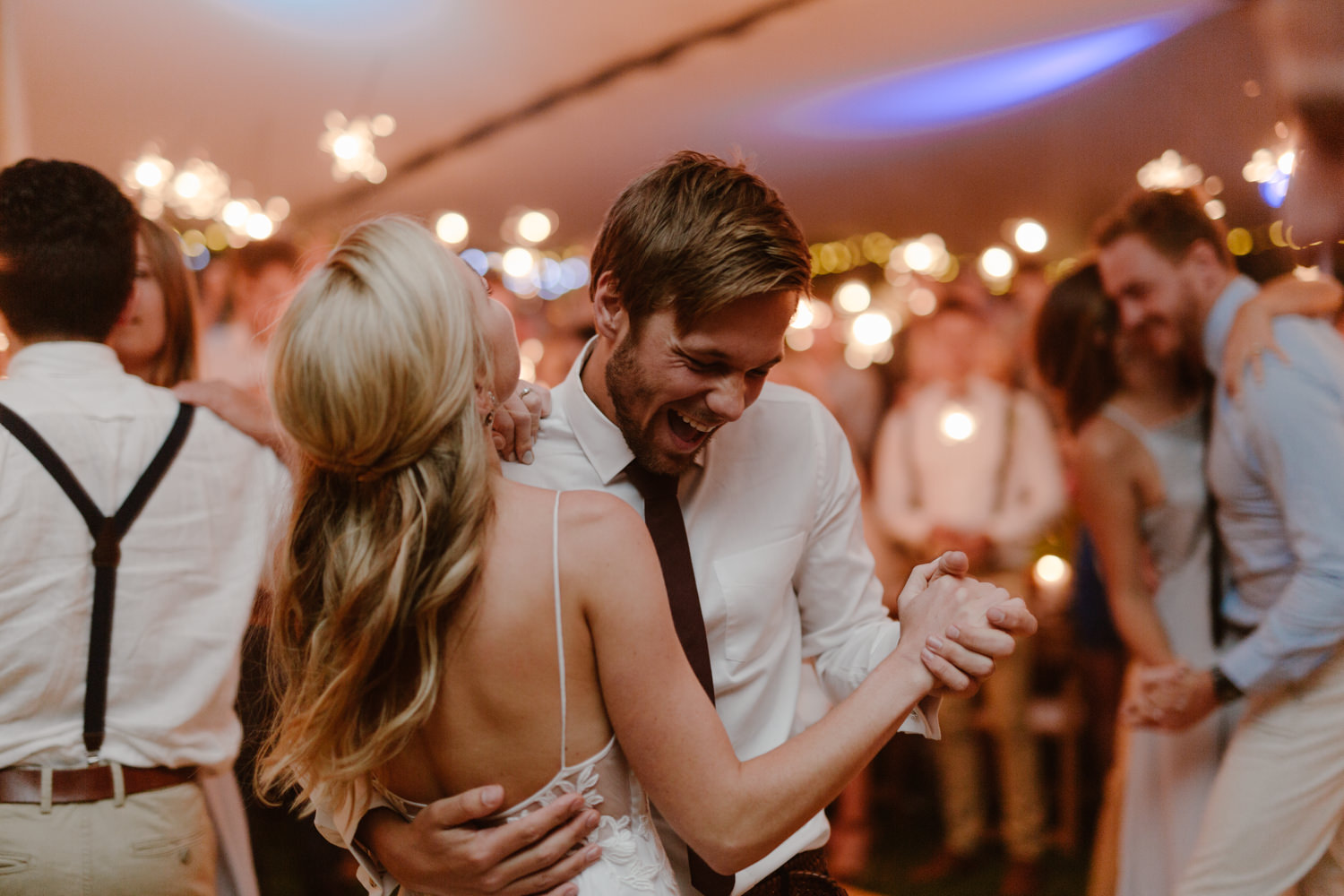 A young bride and groom dancing hand in hand at their wedding.