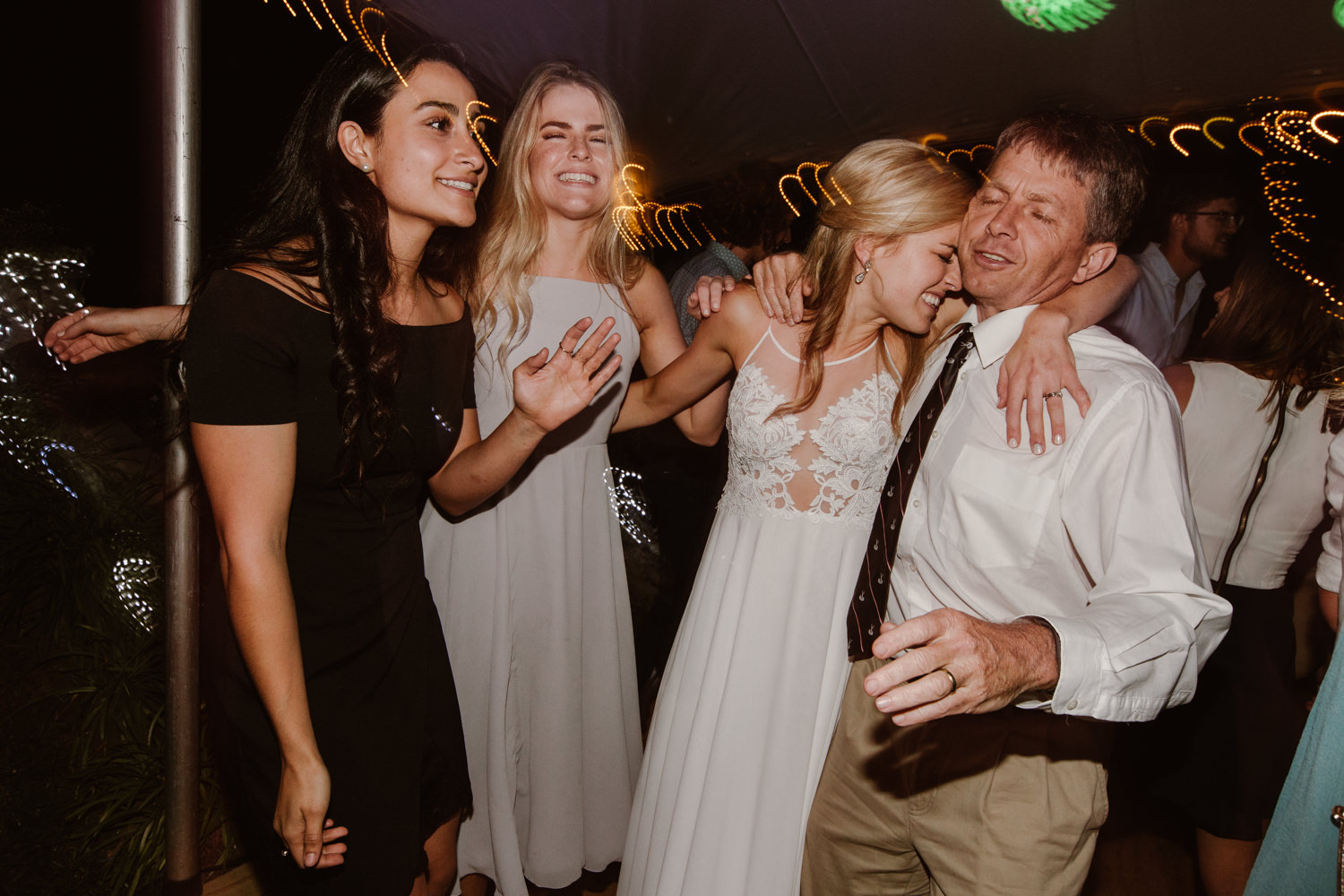 A gorgeous blonde bride crying and emotional on her wedding dance floor with friends.