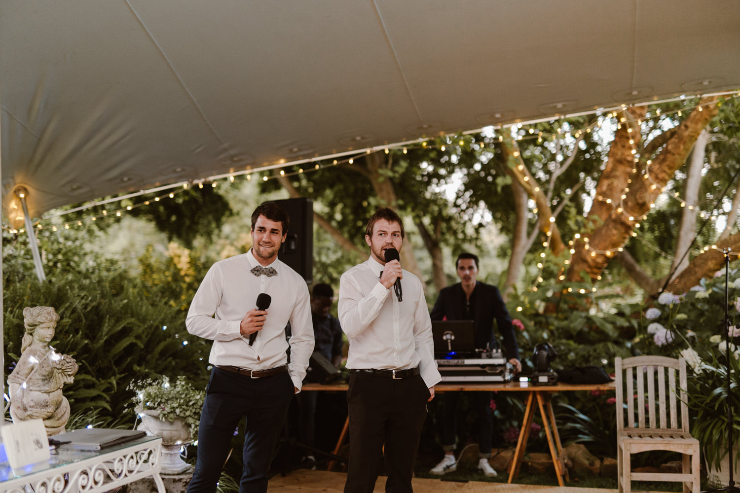 Two groomsmen giving a speech together on two separate wireless microphones.