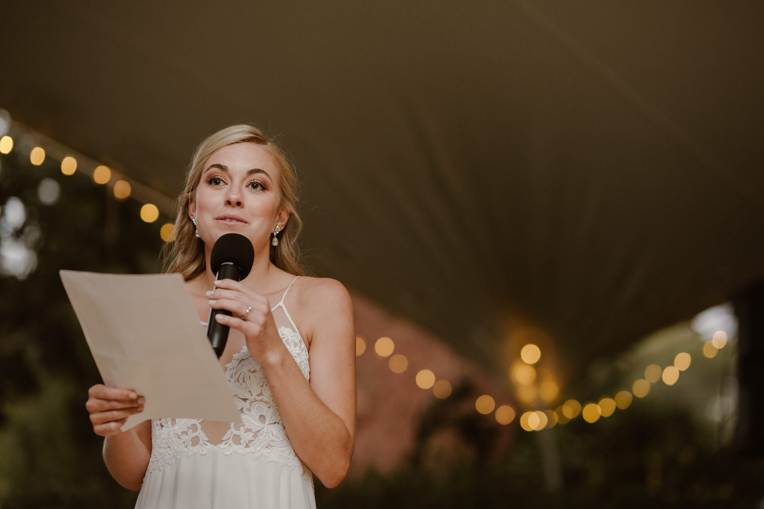 Blonde bride emotional while giving a speech on a clear sound system and microphone.
