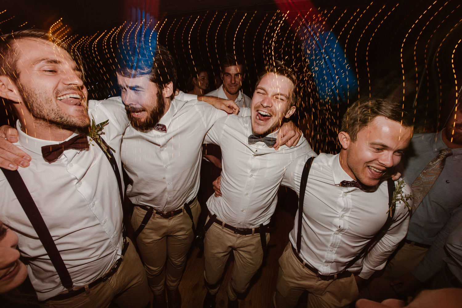 Four groomsmen jumping up and down with lights flashing at a wedding.