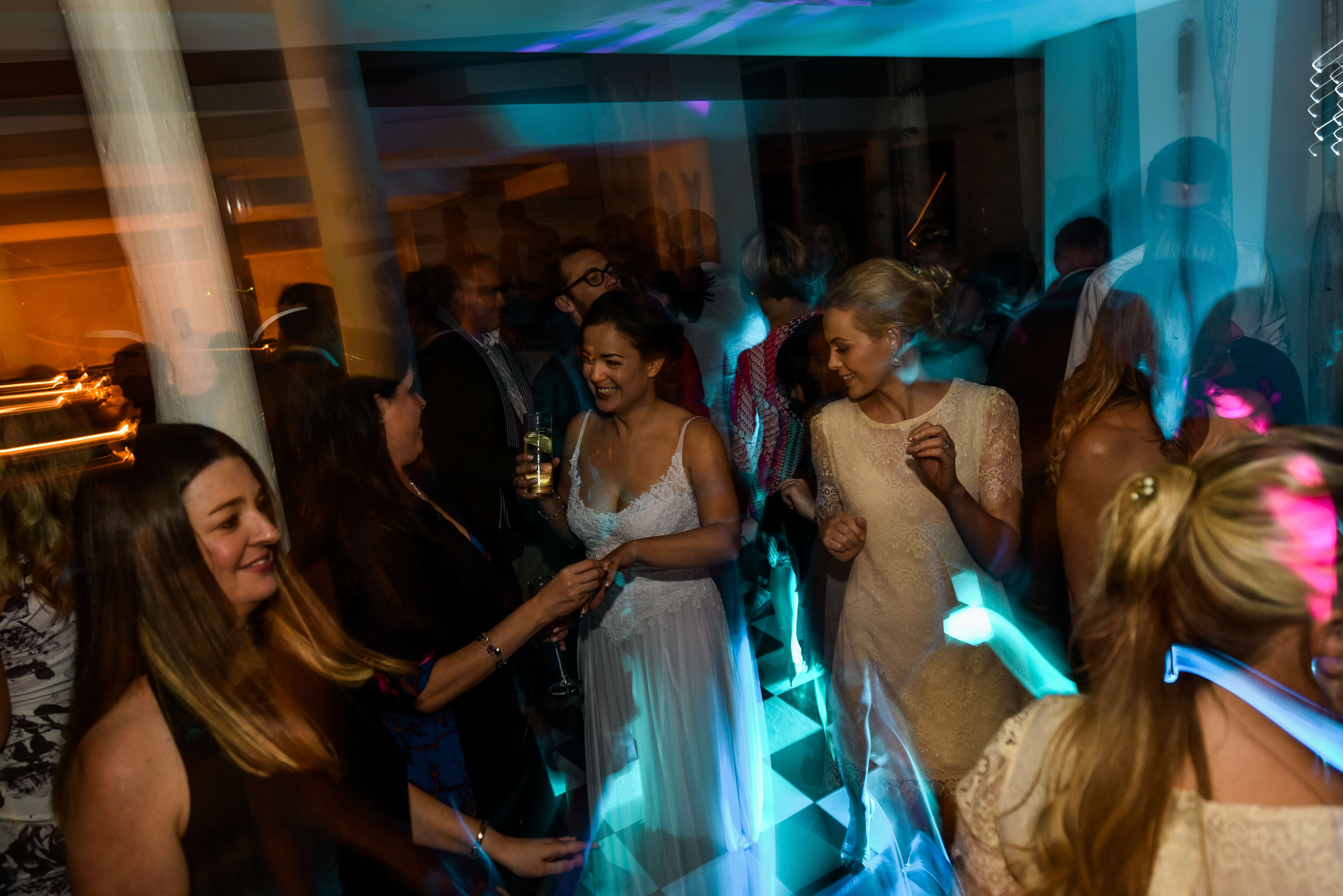 Many women dancing at their friend's wedding to an amazing DJ.