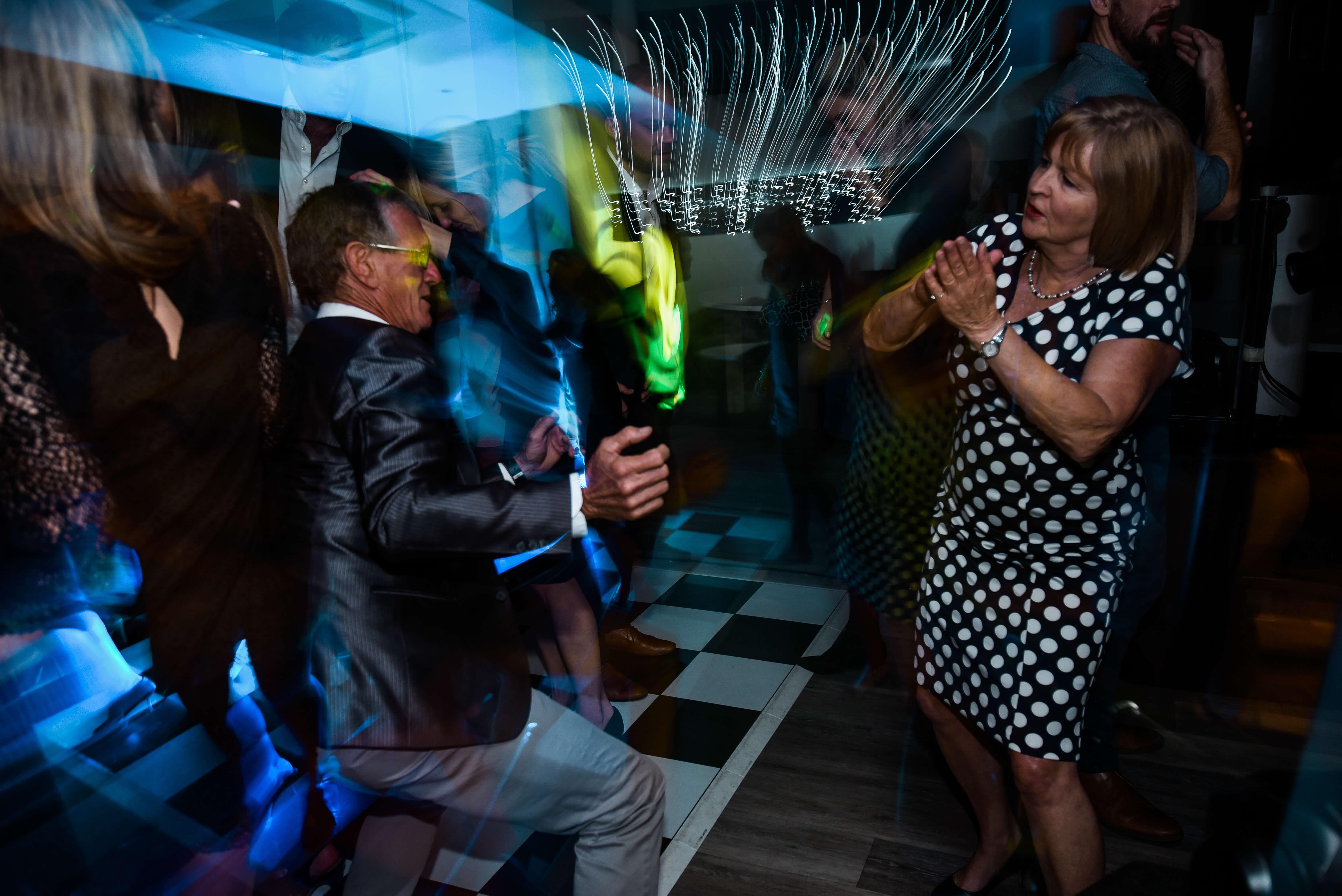 Couple breaking it down on the wedding dance floor with amazing lights.