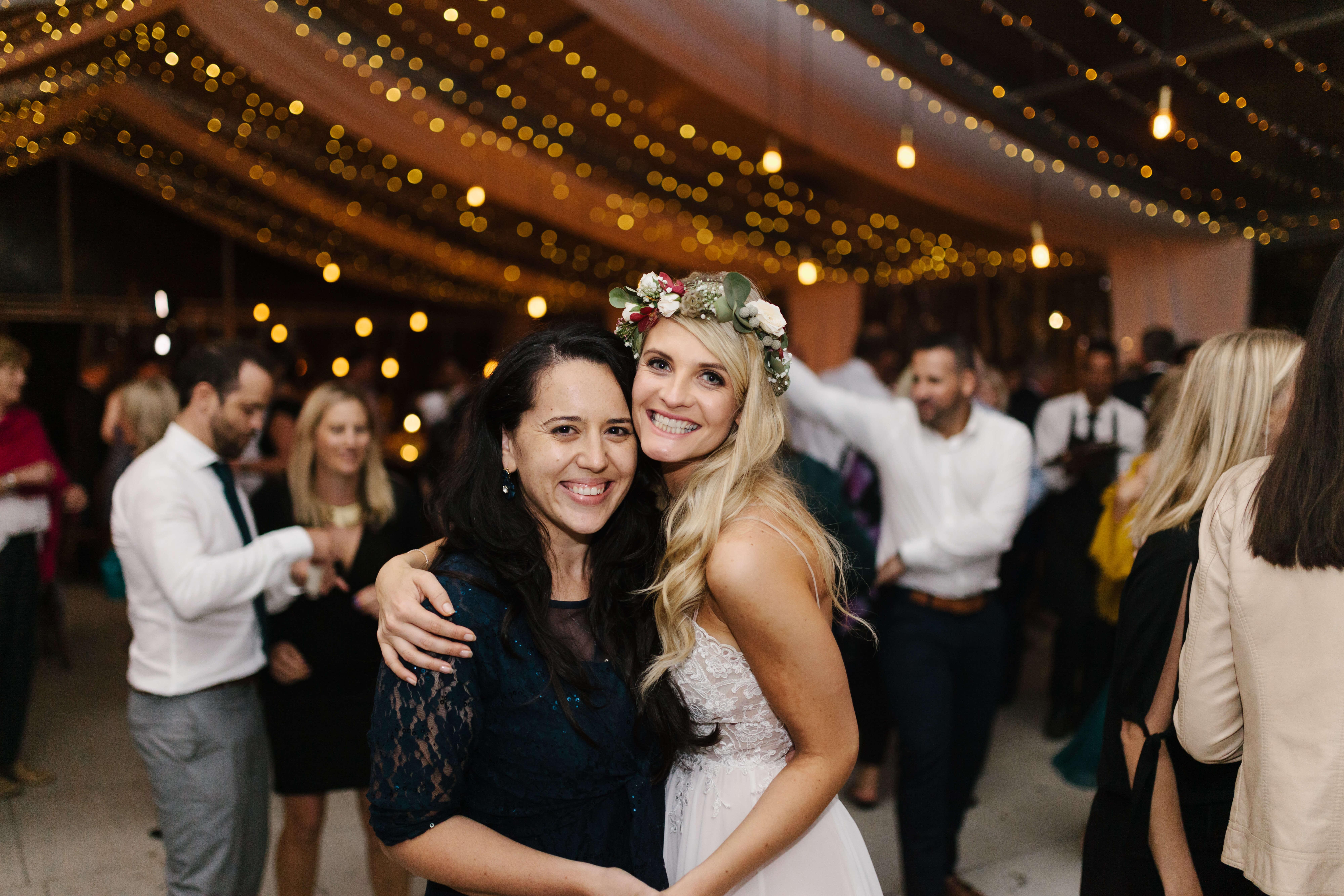 A stunning blonde bride with flowers around her head on a wedding dance floor.