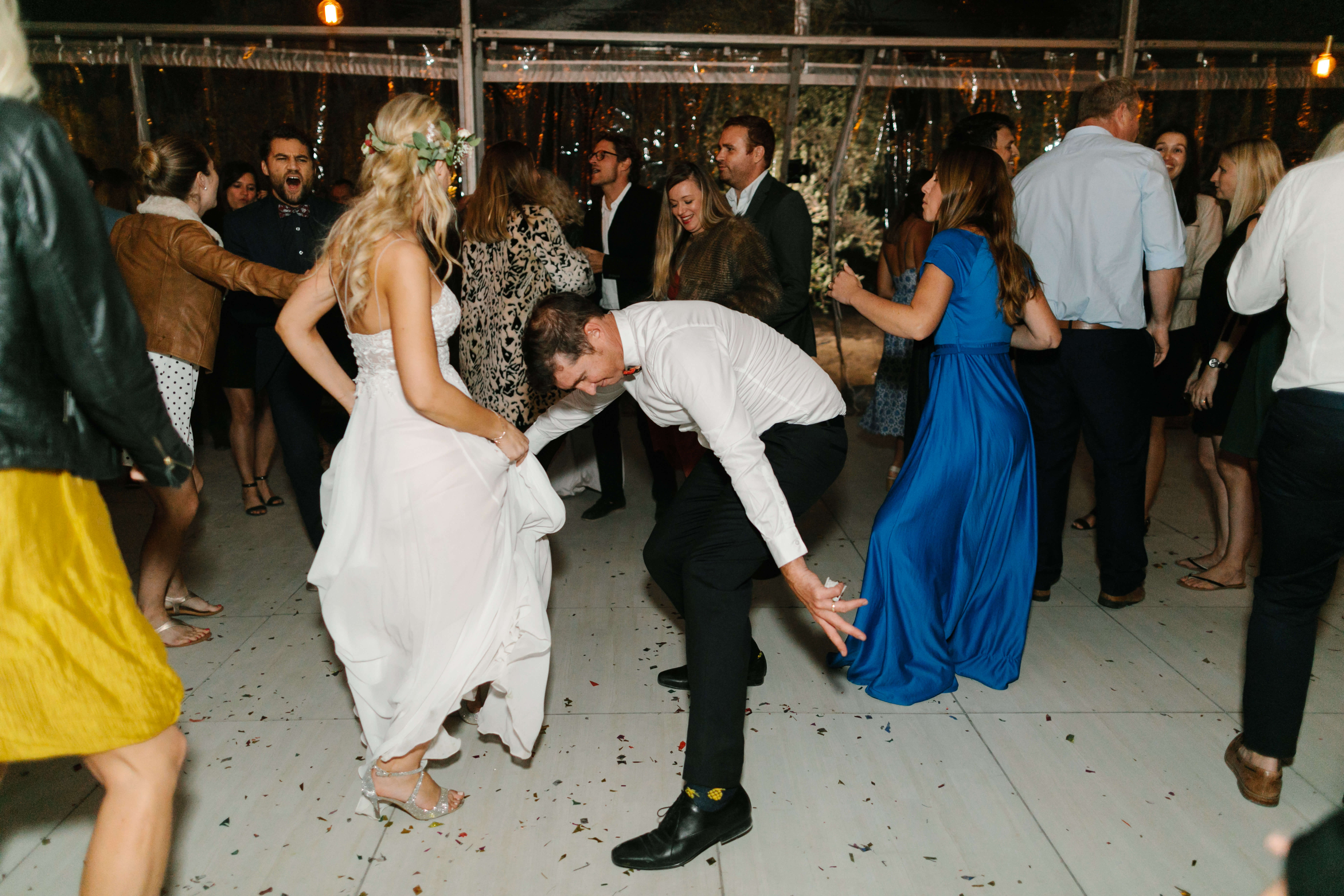 A bride and groom dancing like crazy at their wedding.