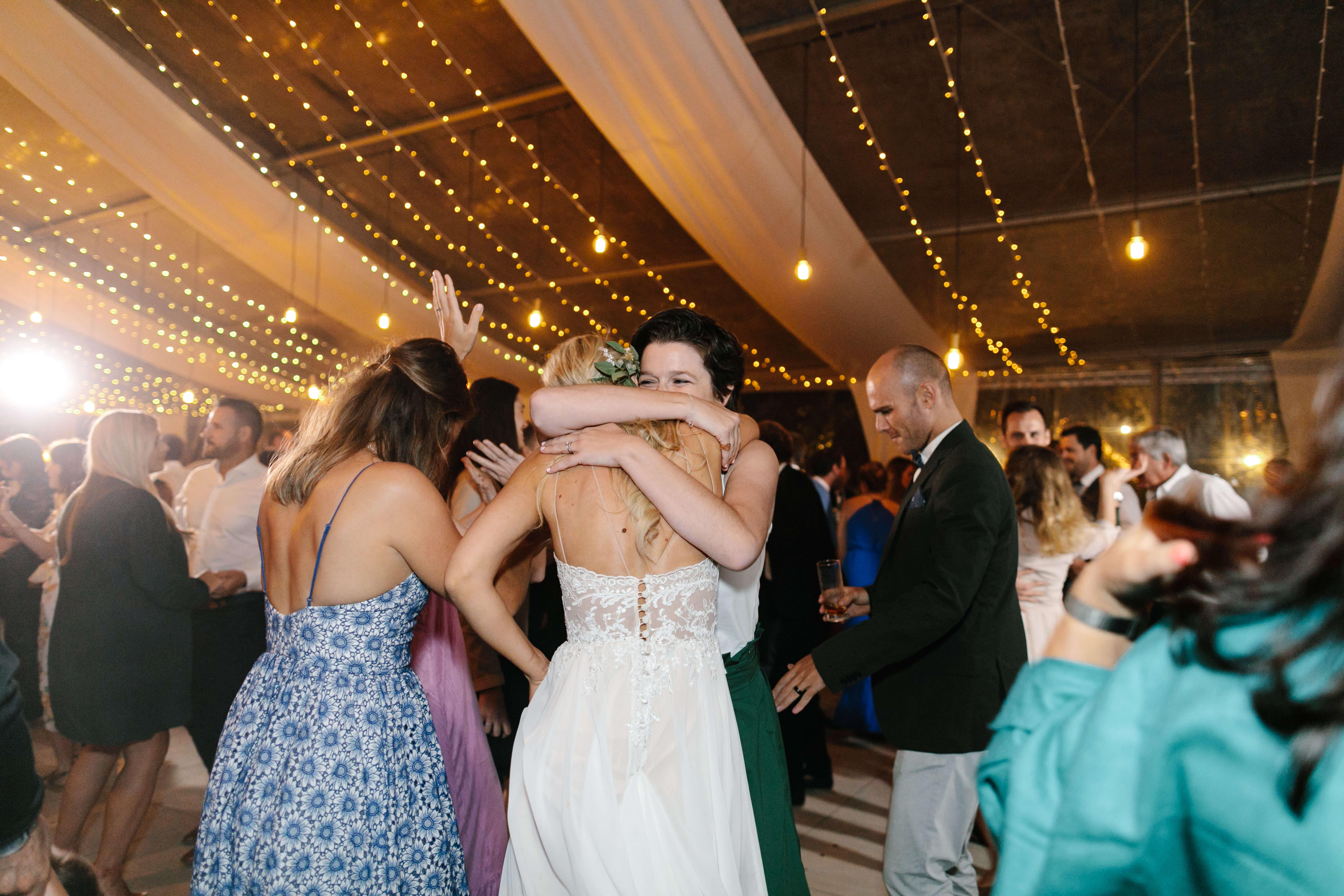 A friend hugging a blonde bride on her wedding night.