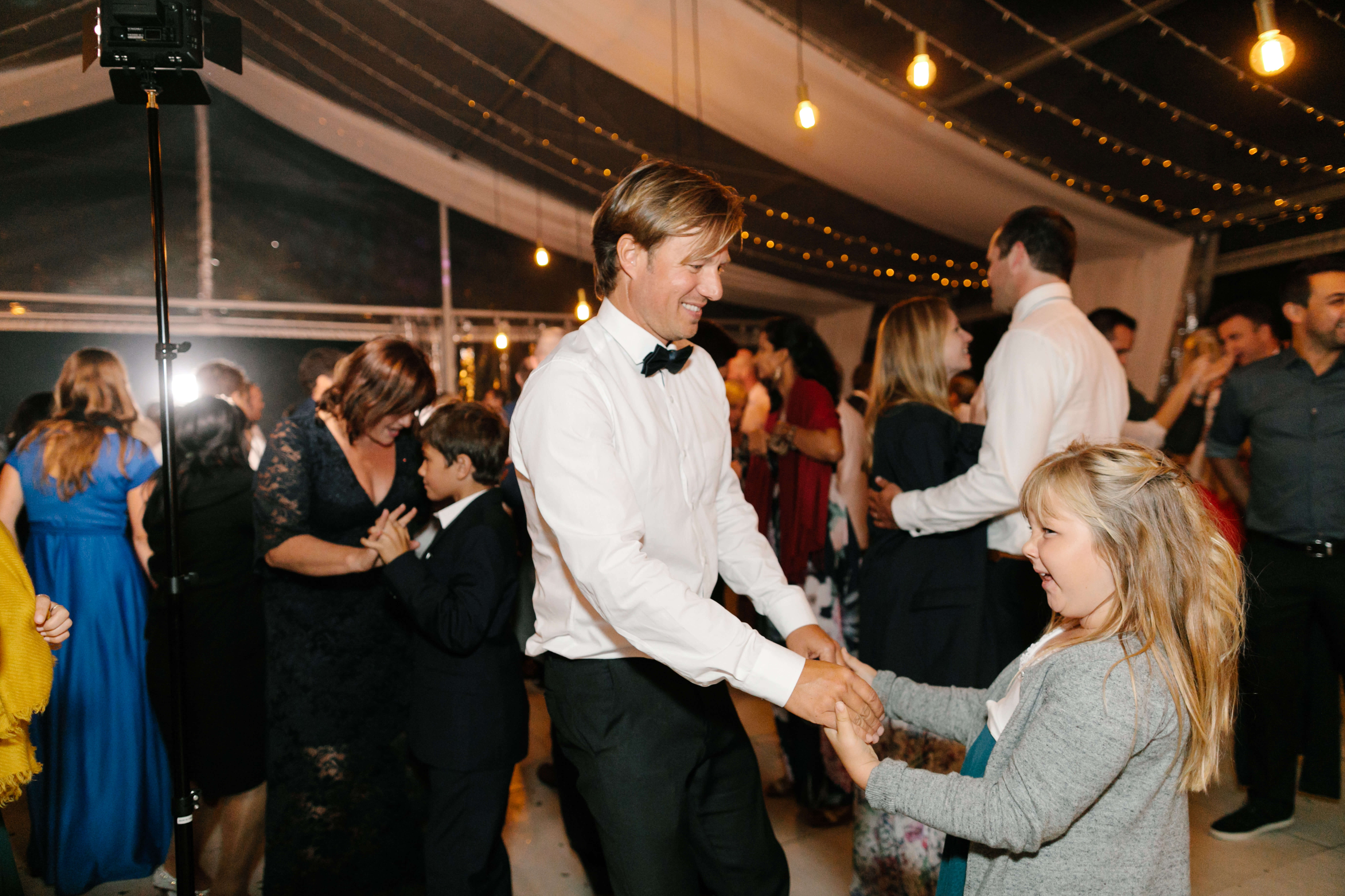 A blonde girl and her dad dancing on a wedding dance floor.