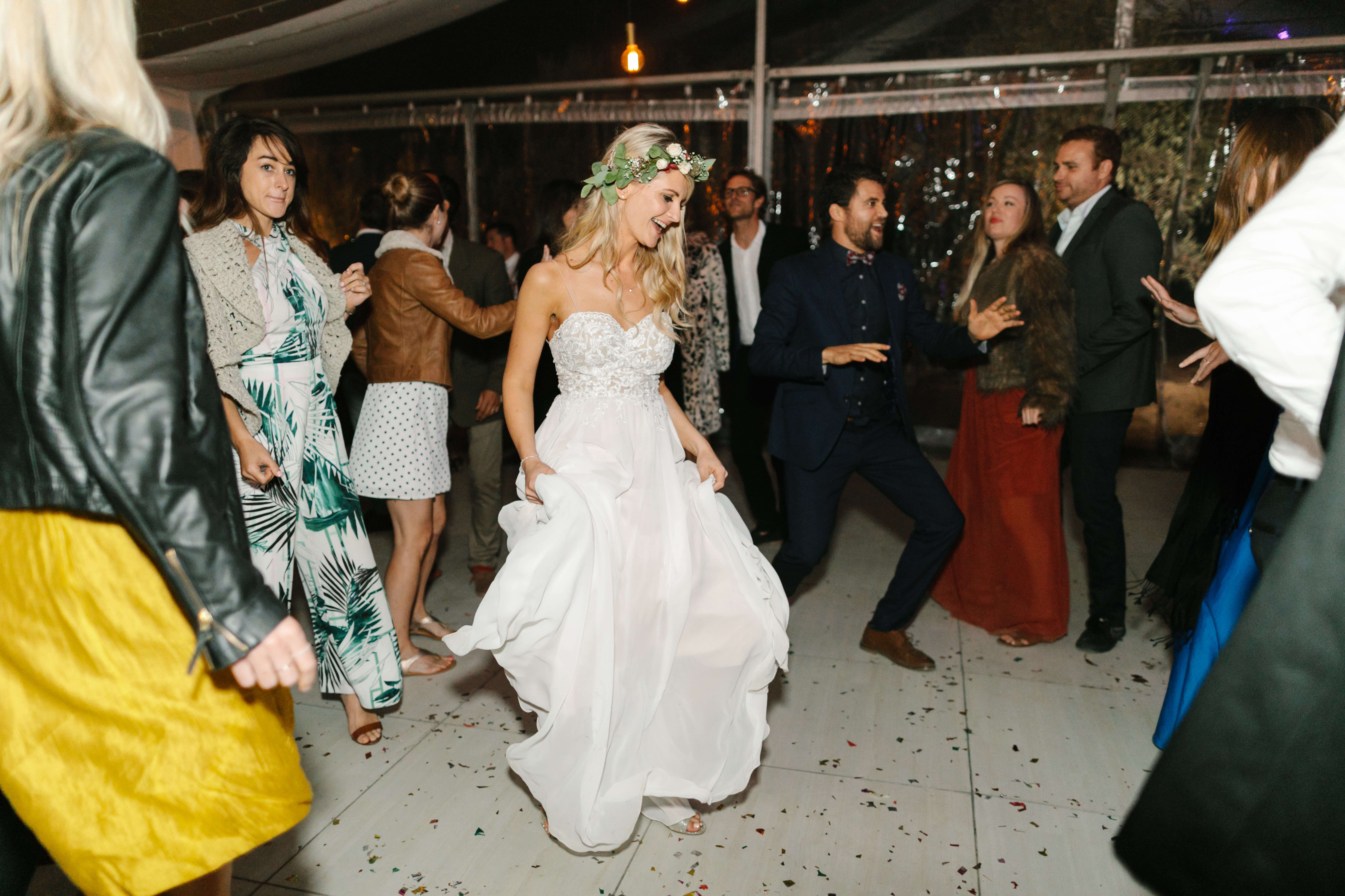 A bride in a white dress dancing on flower petals.