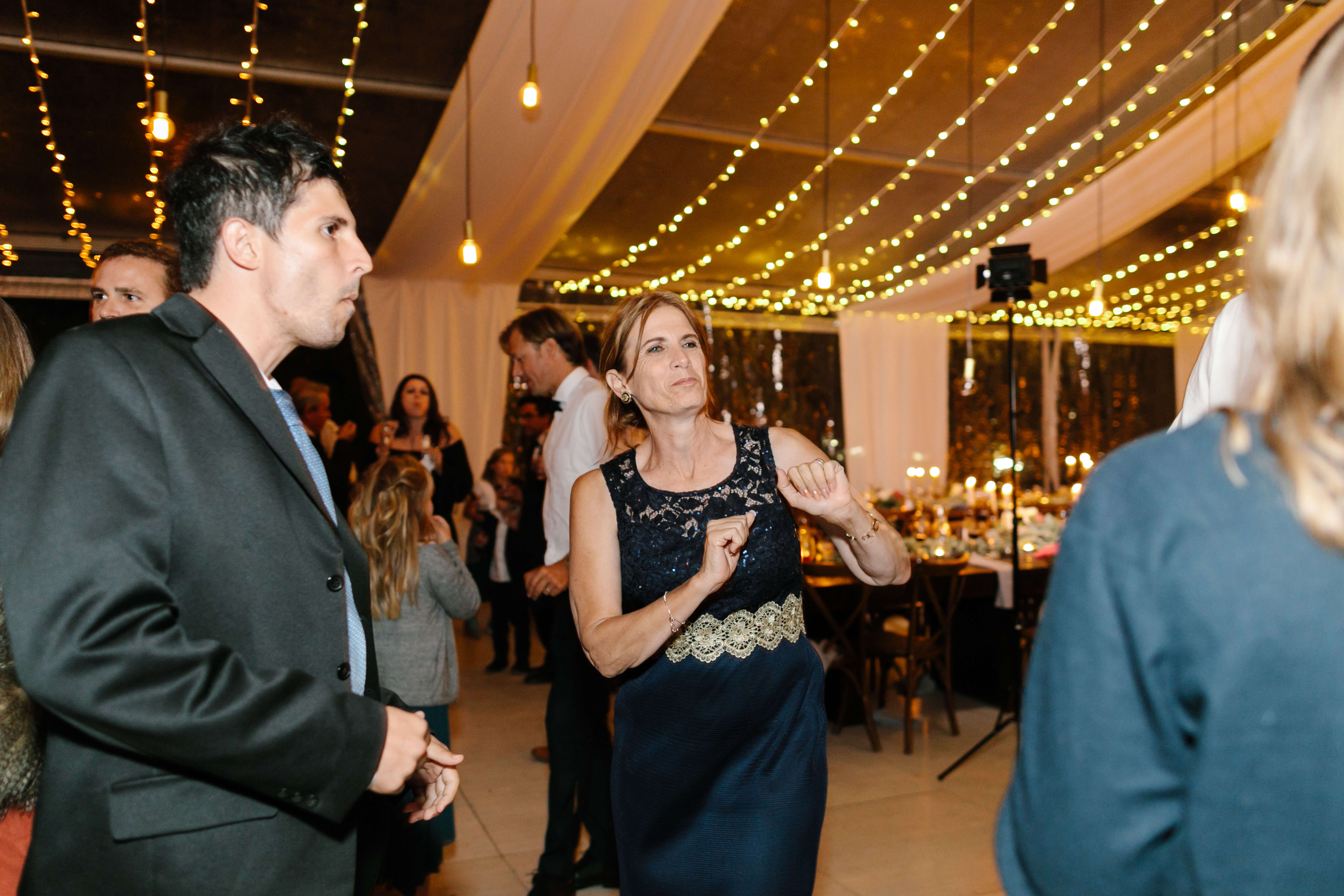 A woman and man dancing funnily at a wedding.