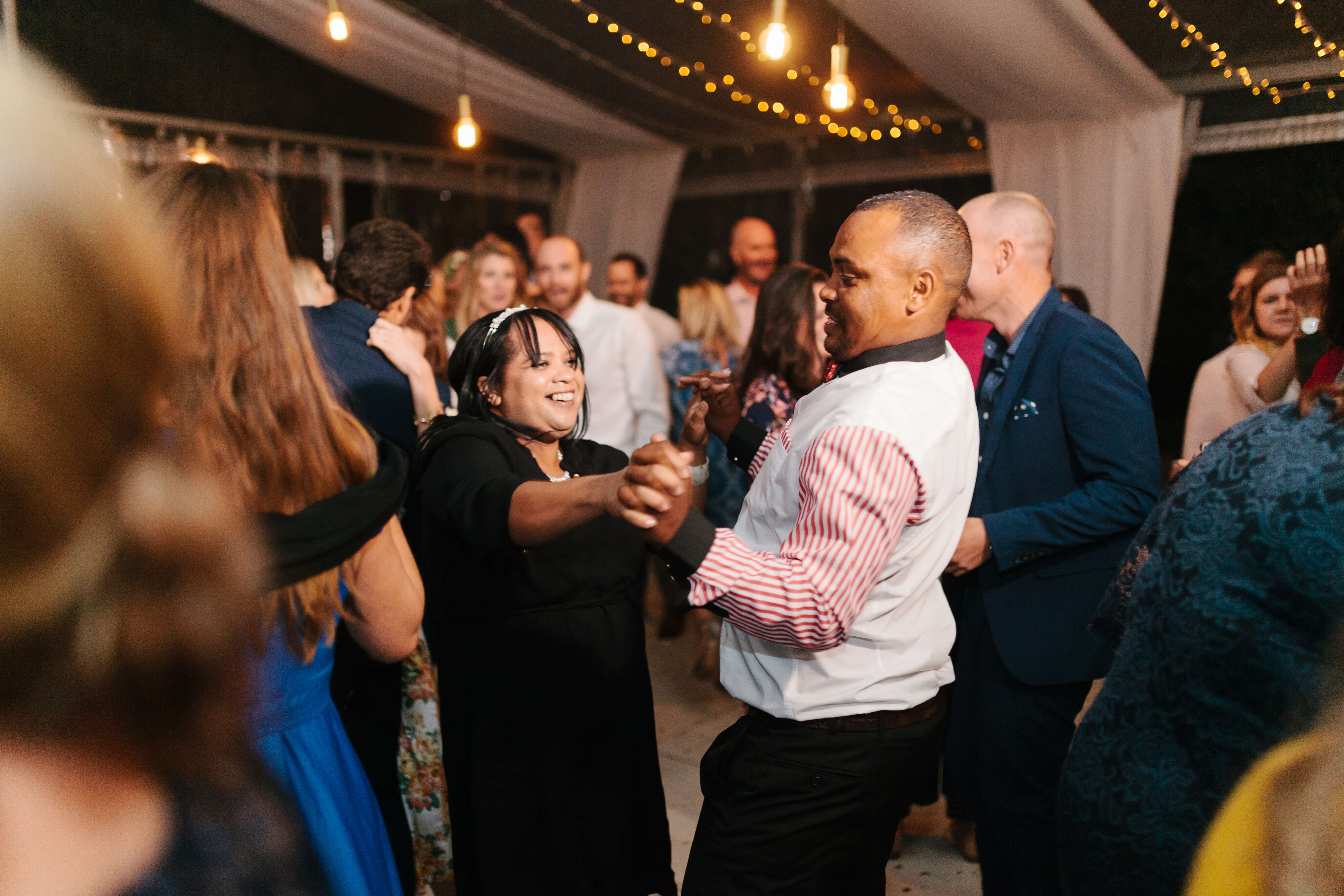 A couple breaking it down on a wedding dance floor to a song they love.