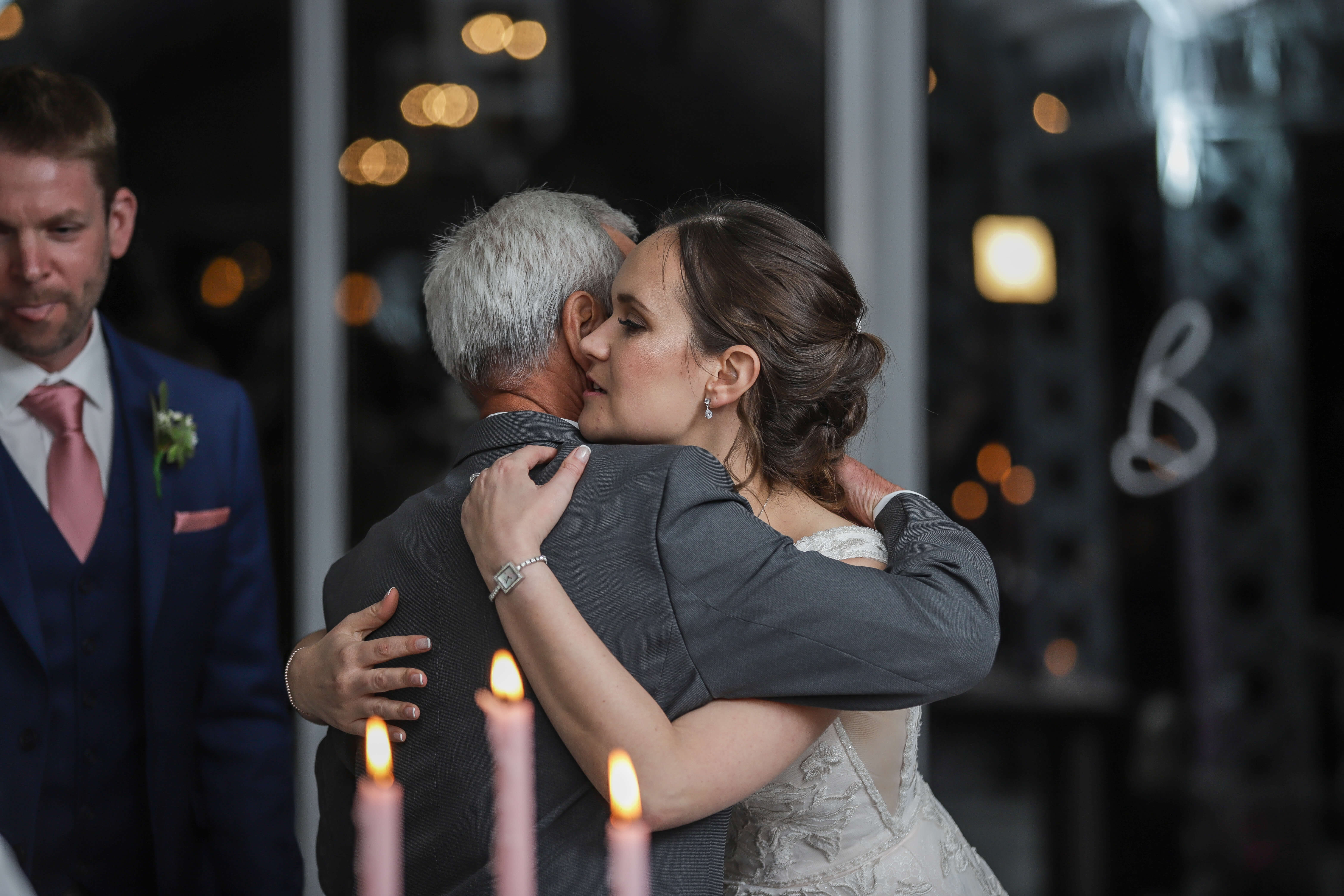 A bride hugging her father after his wedding speech.
