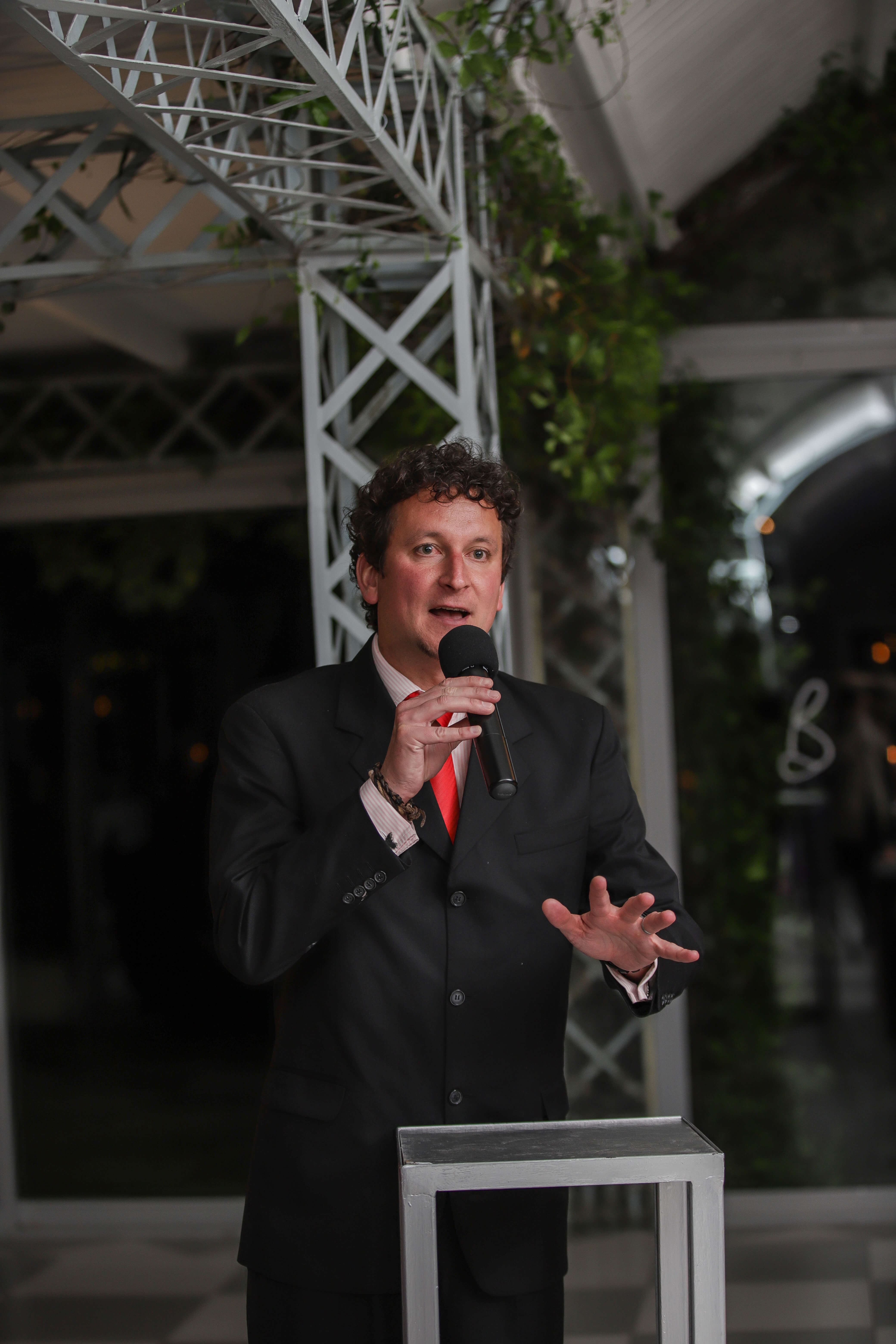 A man in a grey suit with a red tie giving a speech.